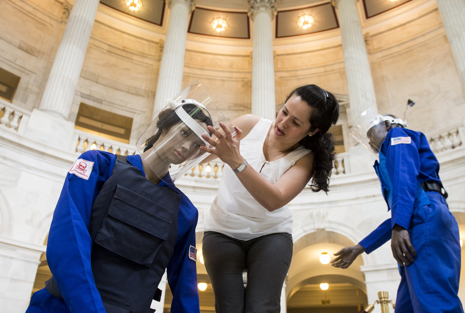 Claudia DelGado, of the Halo Trust, helps set up mannequins for an exhibit in the Russell Senate Office Building in Washington D.C. on May 6, 2013, on ridding the world of land mines.