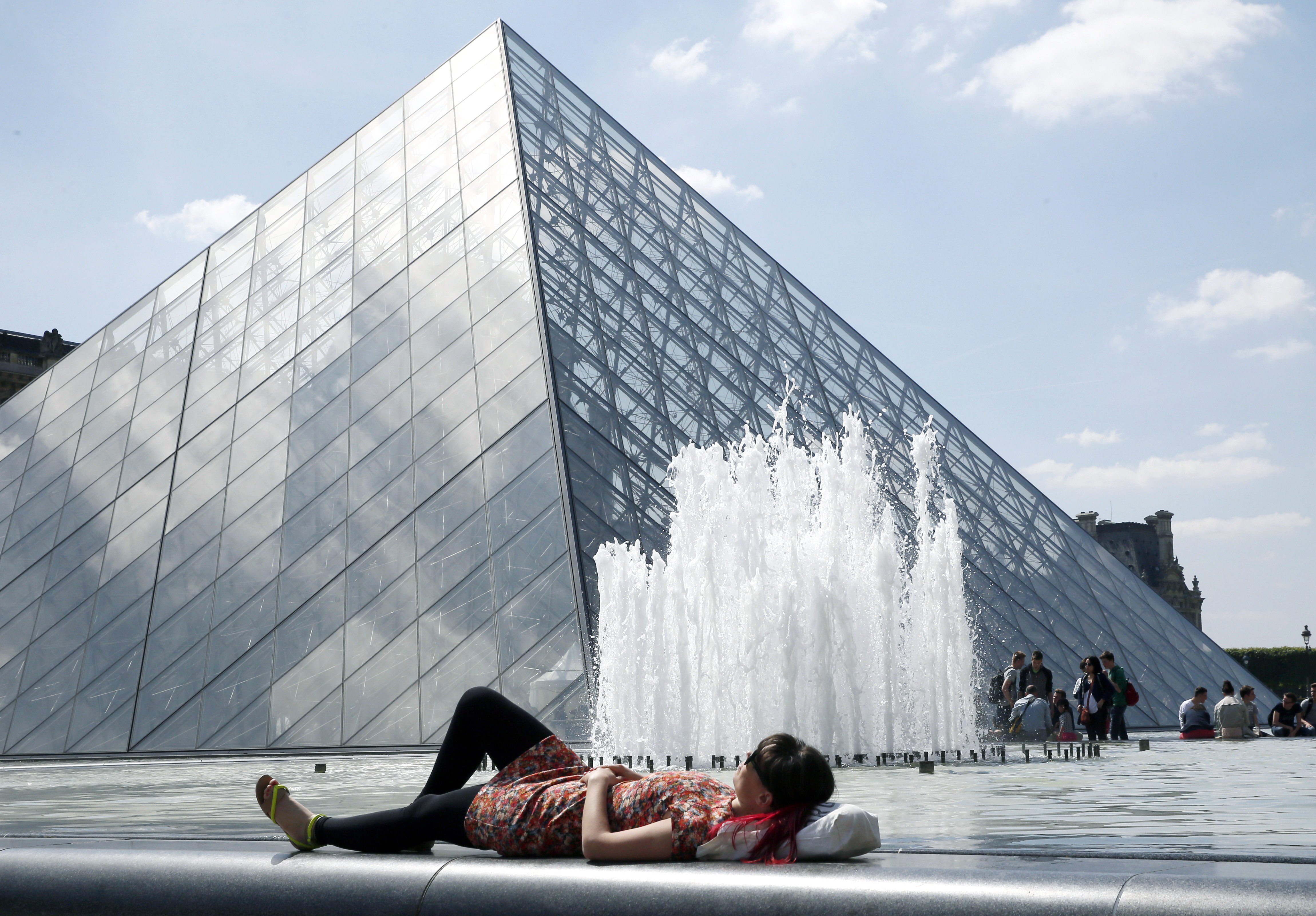 A woman enjoys the sunny weather near the Louvre Museum pyramid in Paris on May 16, 2014.