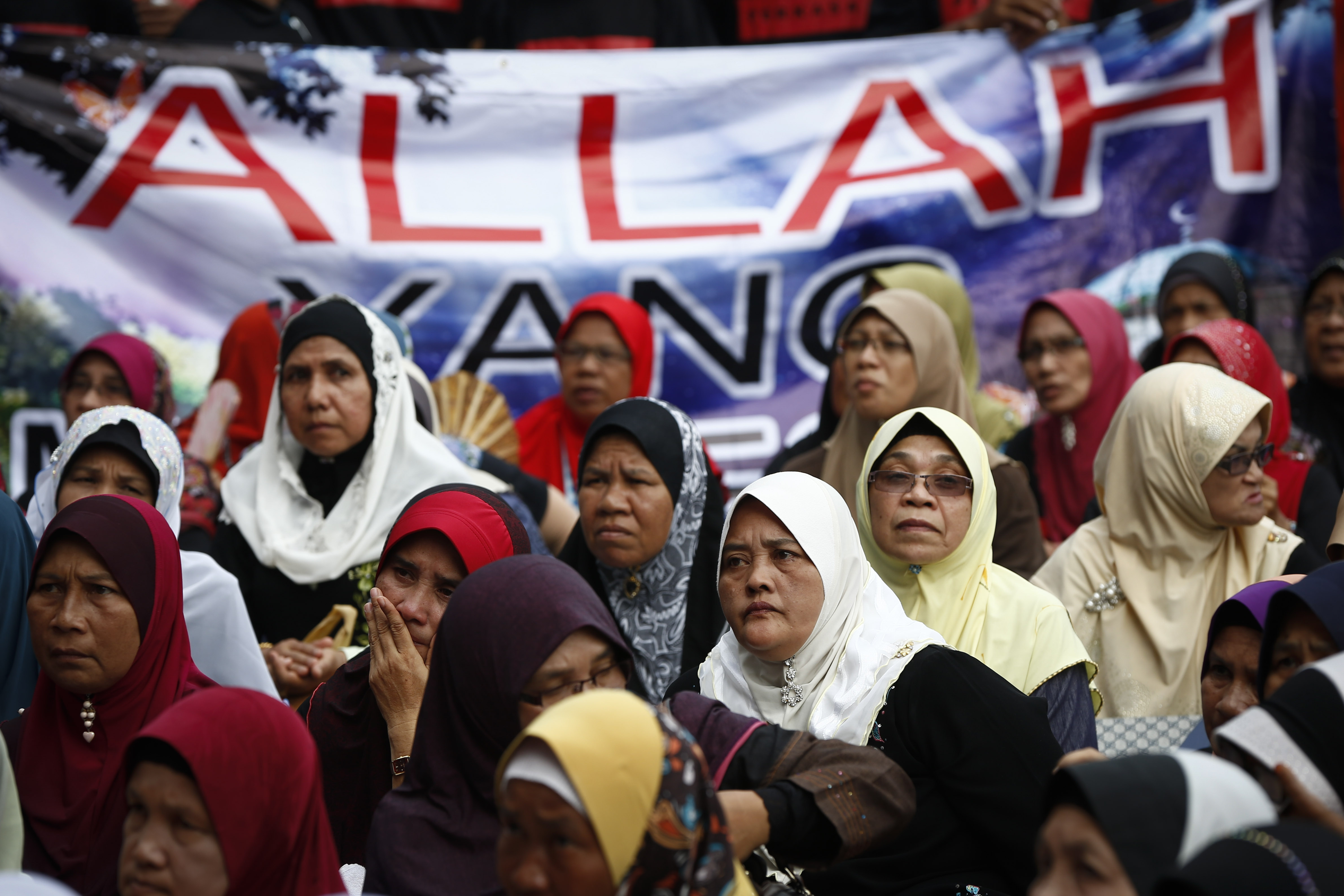 Muslim women sit in front of a banner reading Allah during a protest outside the court of appeal in Putrajaya, outside Kuala Lumpur, on June 23, 2014