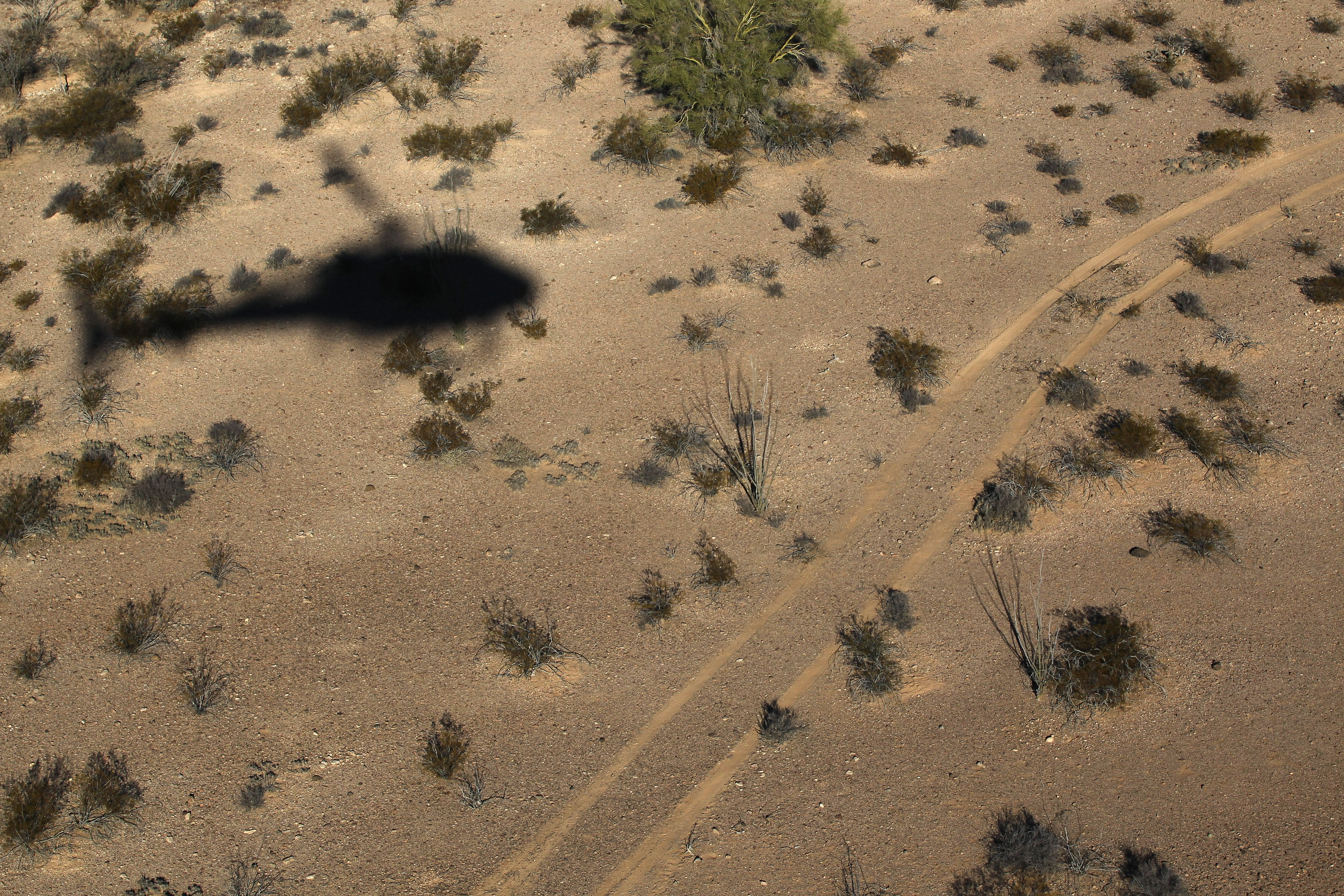 As seen from the air, a helicopter is seen moving north through the Sonoran Desert in Tohono O'odham Nation, Ariz. on December 9, 2010.