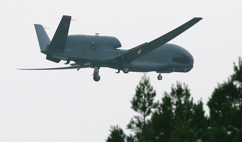 An unmanned surveillance drone 'Global Hawk' flies toward the U.S Misawa Air Base on May 24, 2014 in Misawa, Aomori, Japan. T