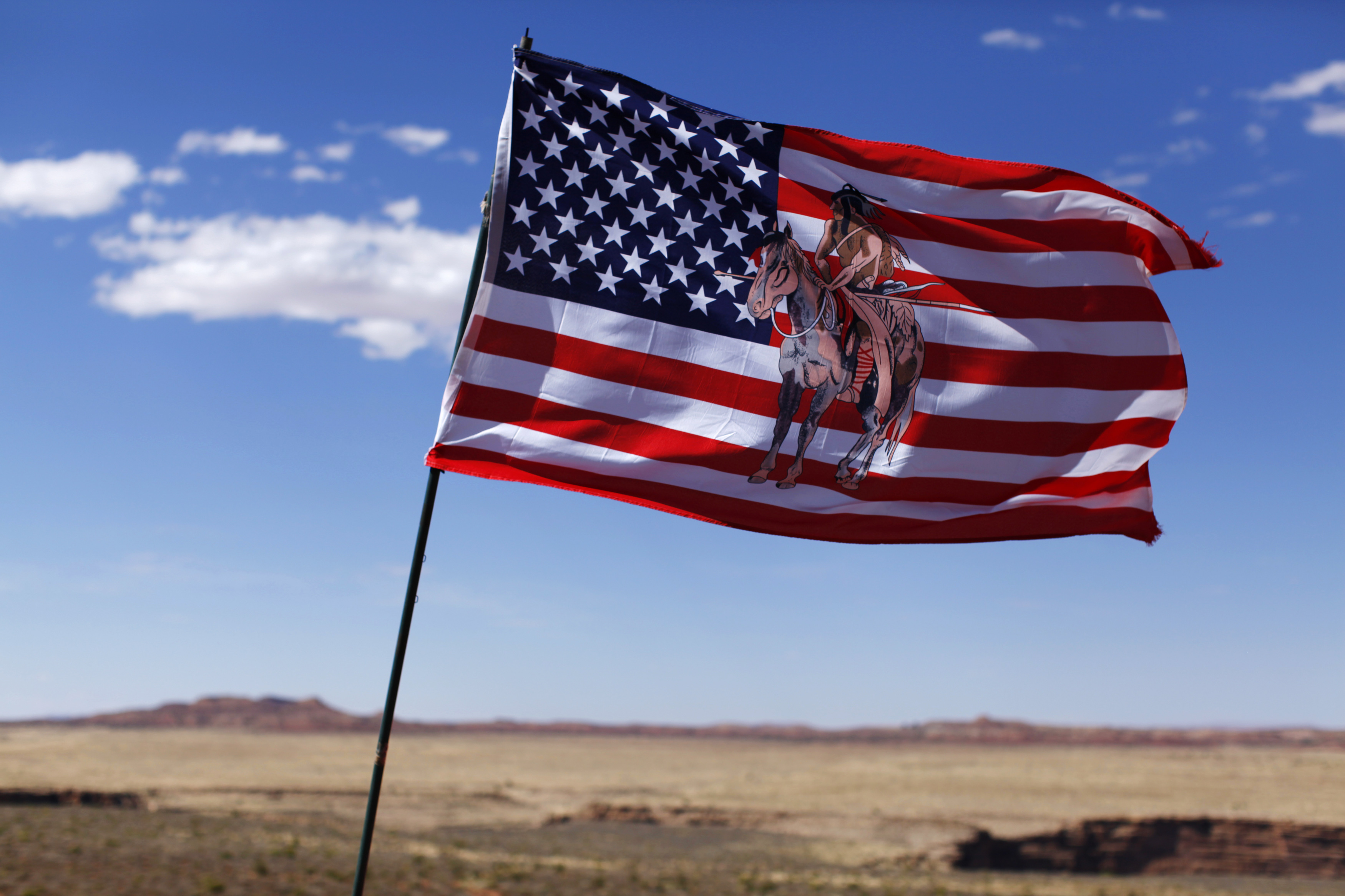A U.S. flag with an image of an American Indian horse rider flies next to a roadside jewellery stand on the Navajo Reservation, by a remote section of the Grand Canyon near Little Colorado River, Ariz., June 23, 2013.