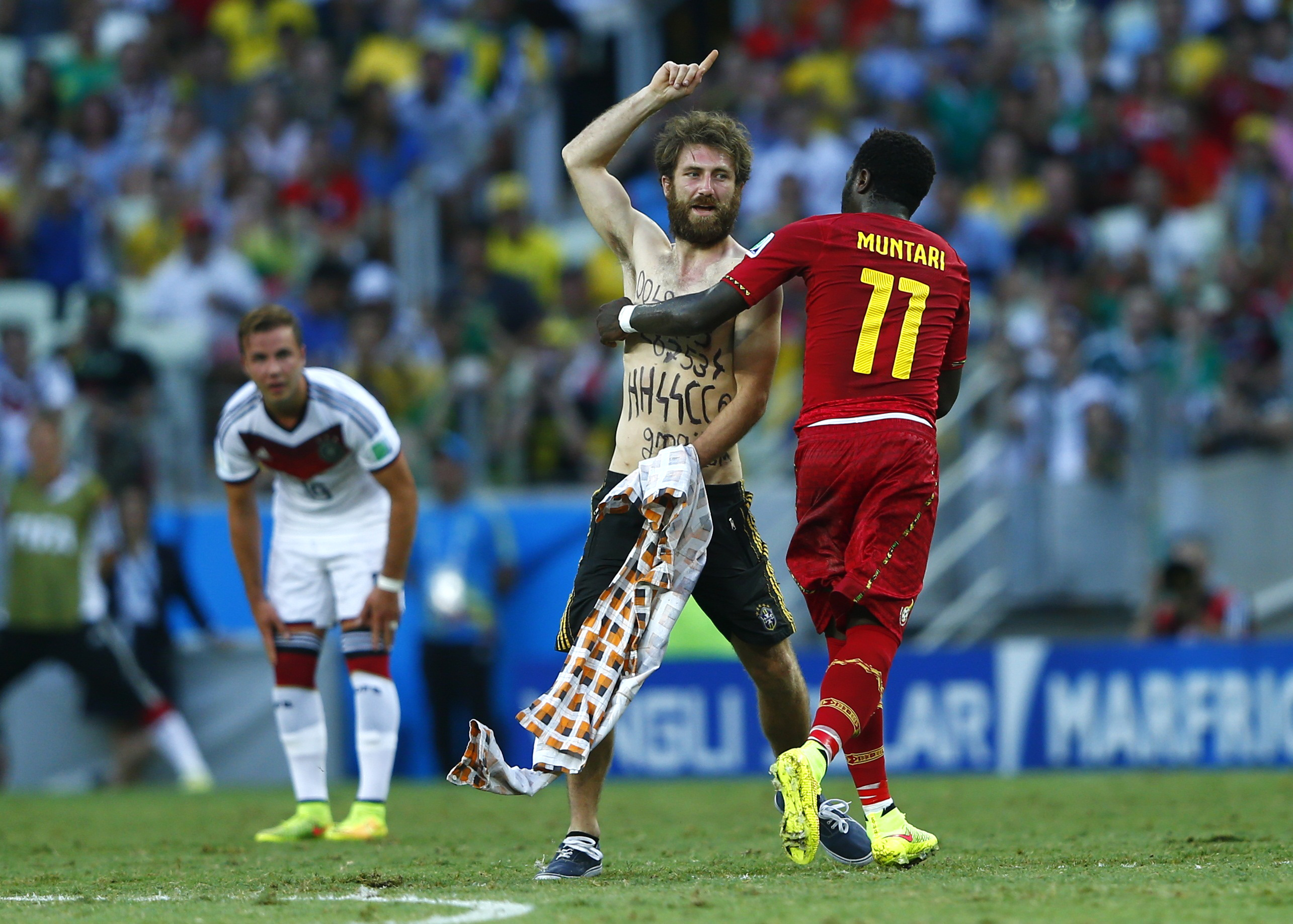 Ghana's Sulley Muntari helps a spectator off the field during the 2014 World Cup soccer match between Germany and Ghana on June 21, 2014.