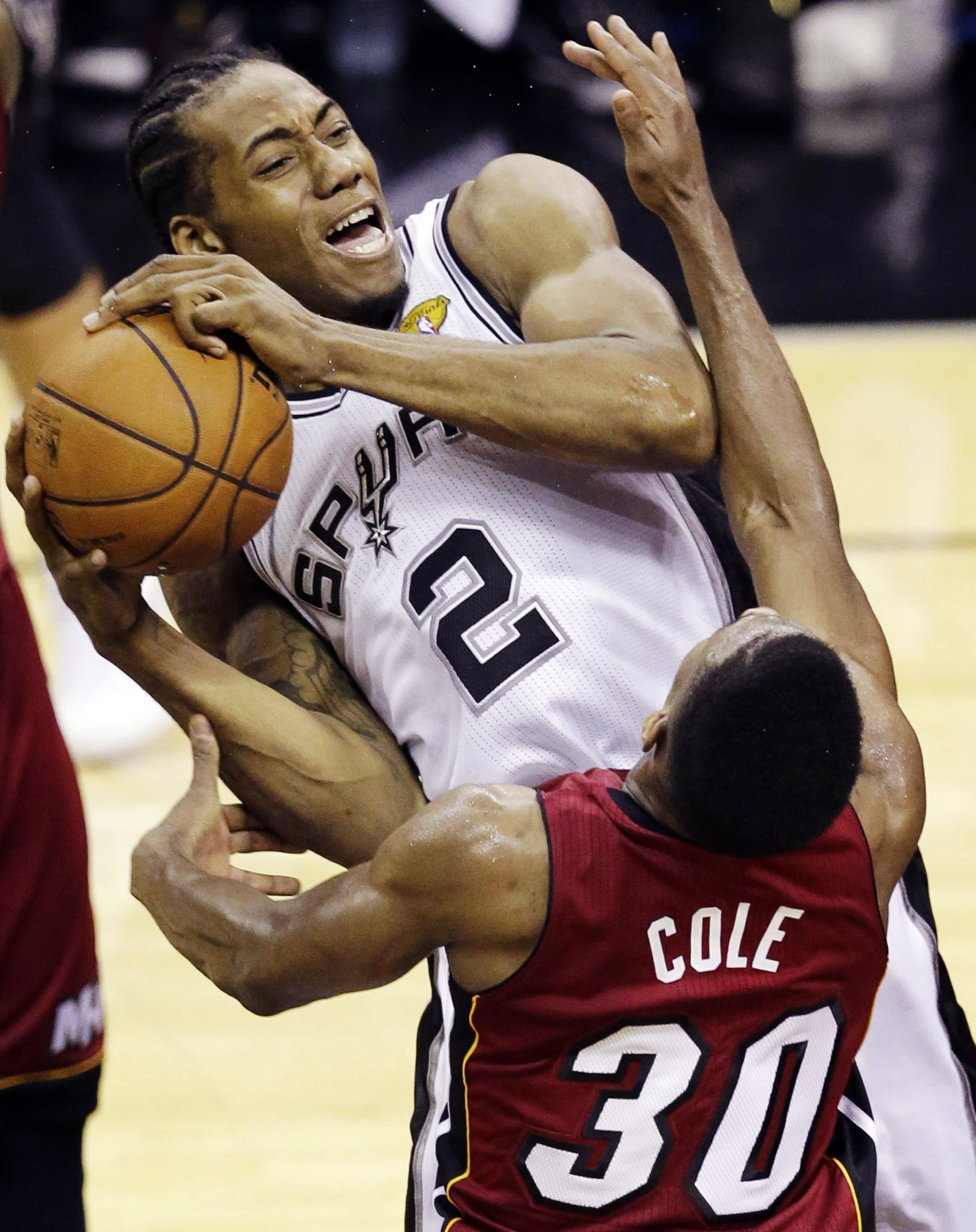 San Antonio Spurs forward Kawhi Leonard (2) is defended by Miami Heat guard Norris Cole (30) during the second half in Game 1 of the NBA basketball finals  in San Antonio on June 5, 2014.