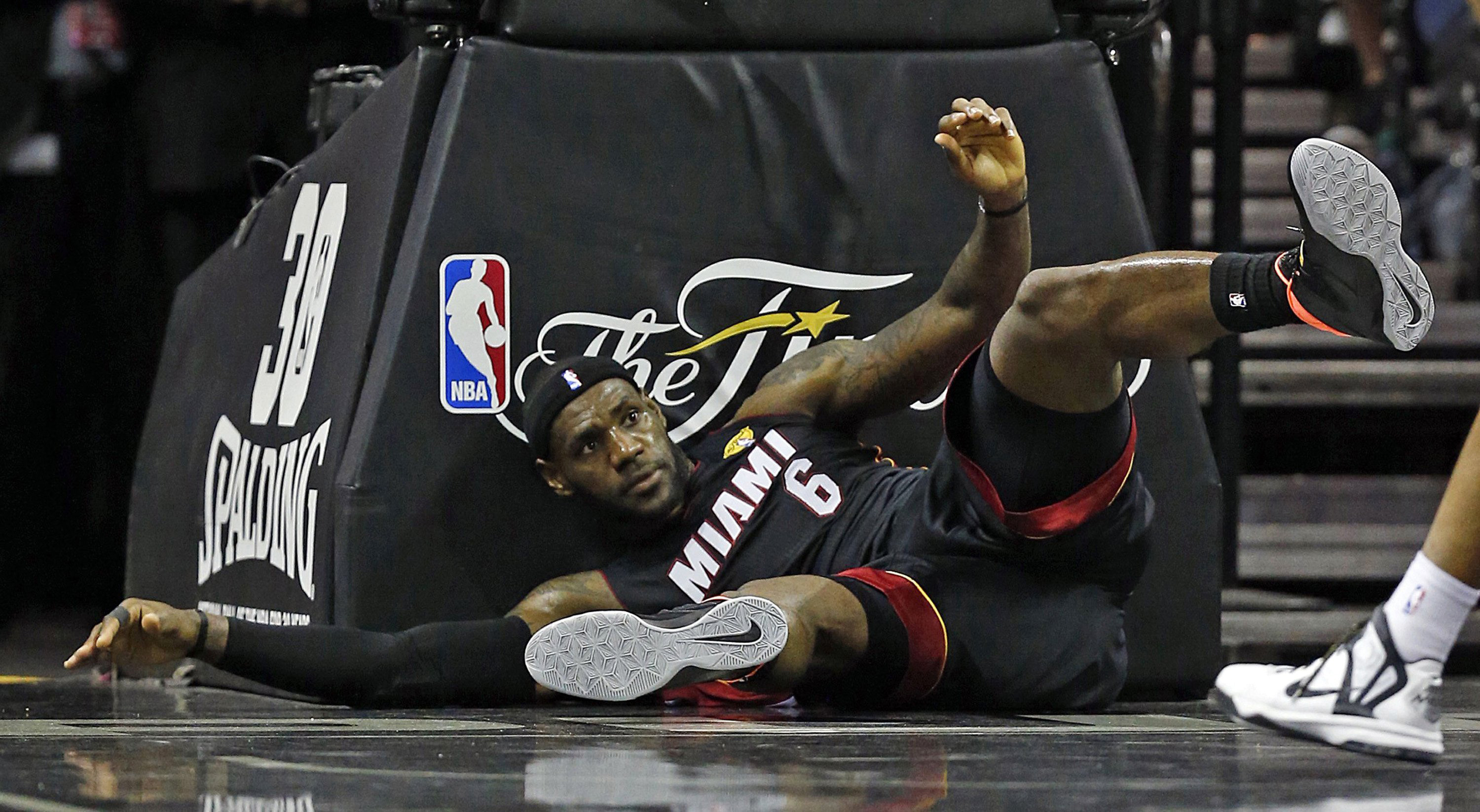 Miami Heat's LeBron James falls to the court during the first quarter in Game 2 of the NBA Finals in San Antonio on June 8, 2014.