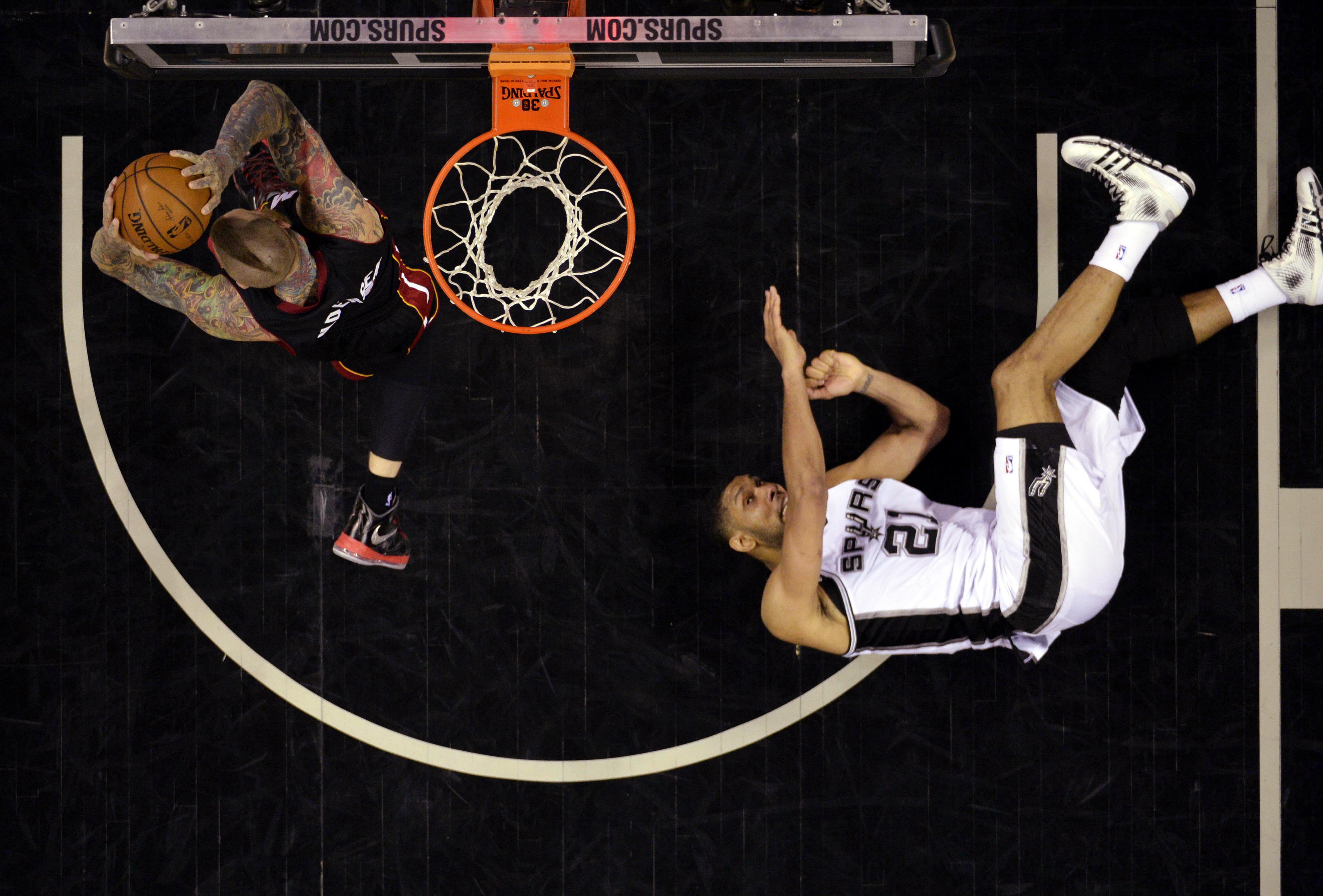 Miami Heat center Chris Andersen (11) grabs a rebound as San Antonio Spurs forward Tim Duncan (21) falls to the floor in Game 2 of the 2014 NBA Finals in San Antonio on June 8, 2014.