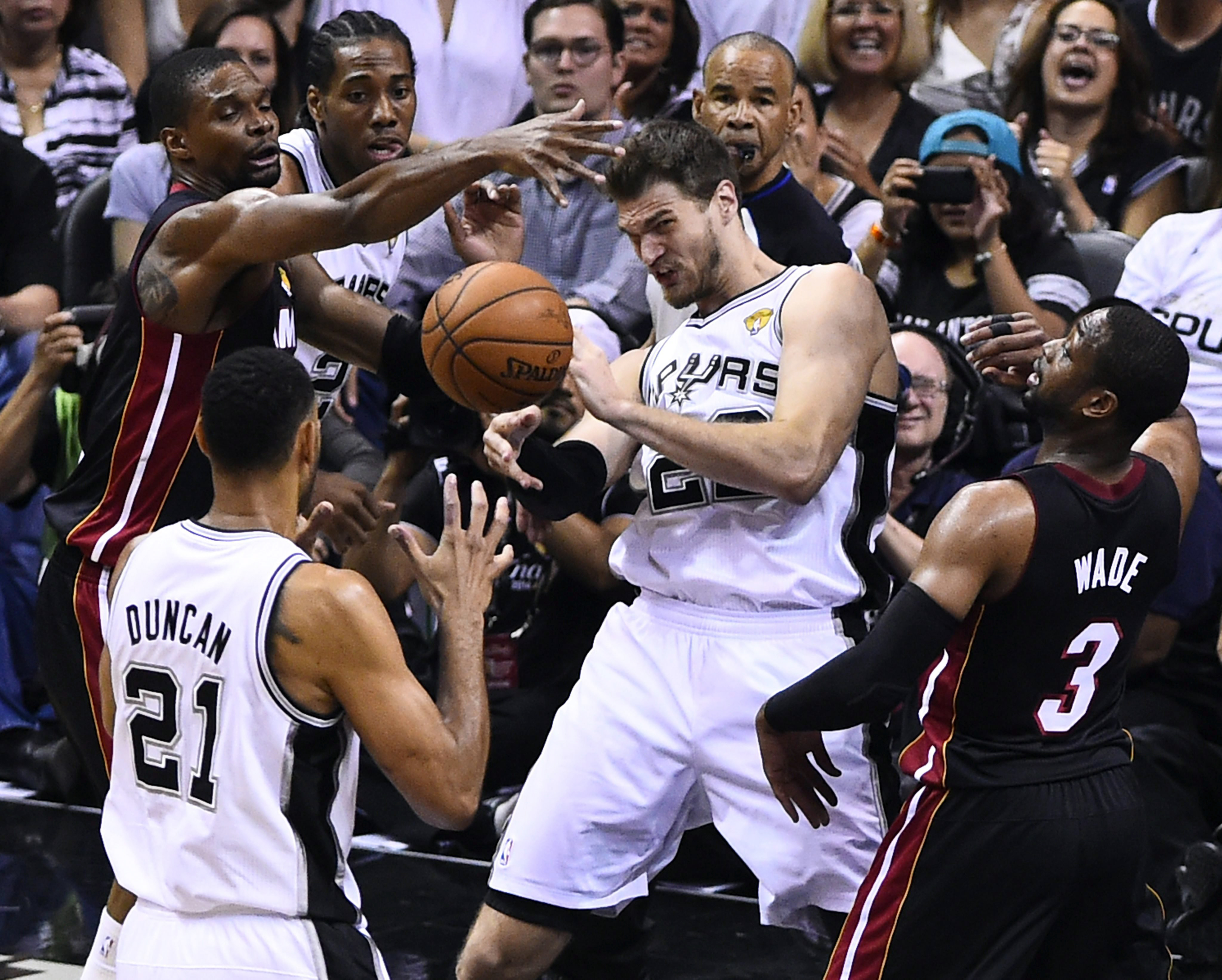 San Antonio Spurs center Tiago Splitter (C) passes off to San Antonio Spurs forward Tim Duncan (2-L) as Miami Heat center Chris Bosh (L) and Miami Heat guard Dwyane Wade (R) defend in the first half of their NBA Finals Game 2 in San Antonio on June 8, 2014.