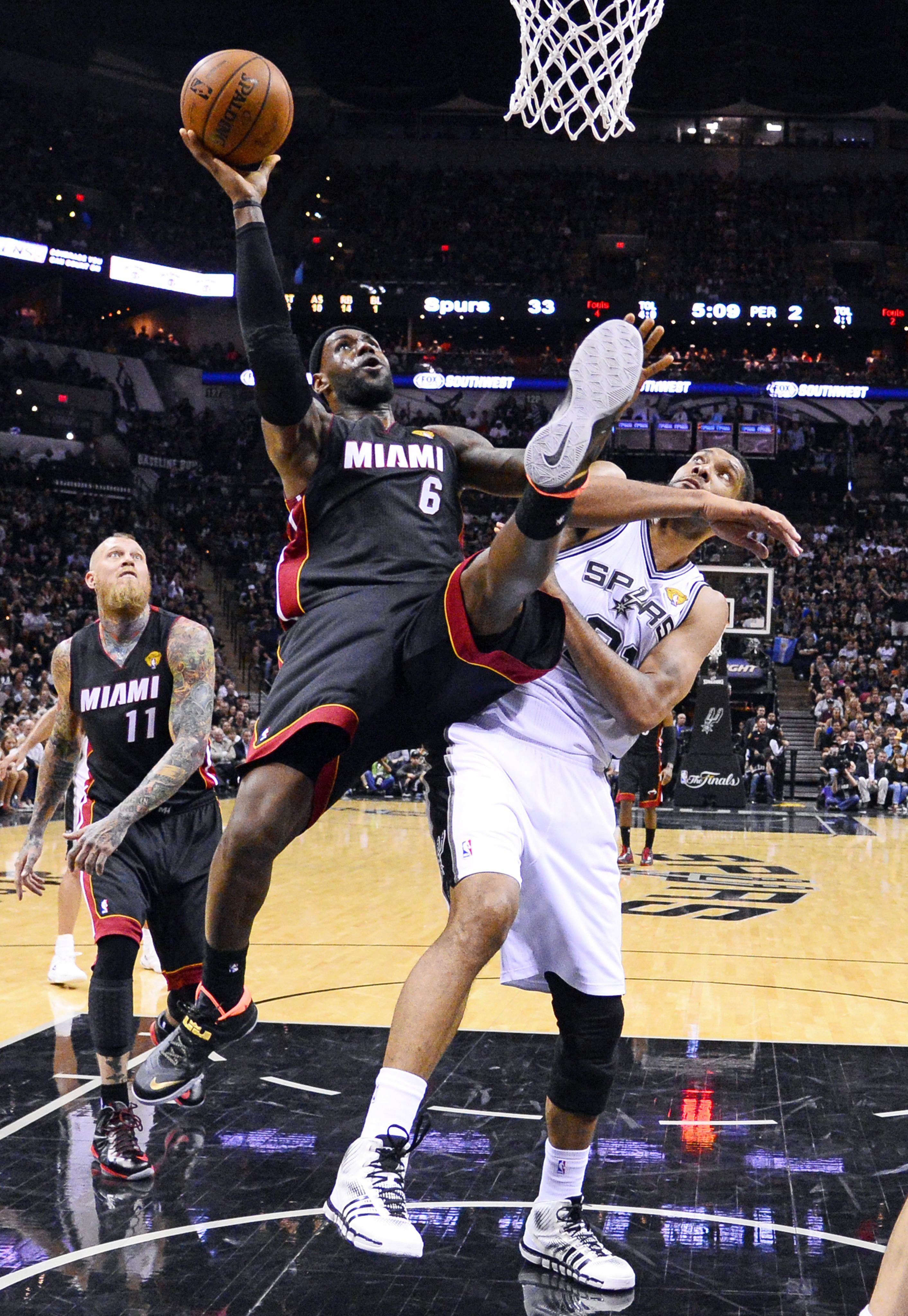 Miami Heat forward LeBron James (C) goes to the basket as San Antonio Spurs forward Tim Duncan (R) defends in the first half of their NBA Finals Game 2 in San Antonio on June 8, 2014.