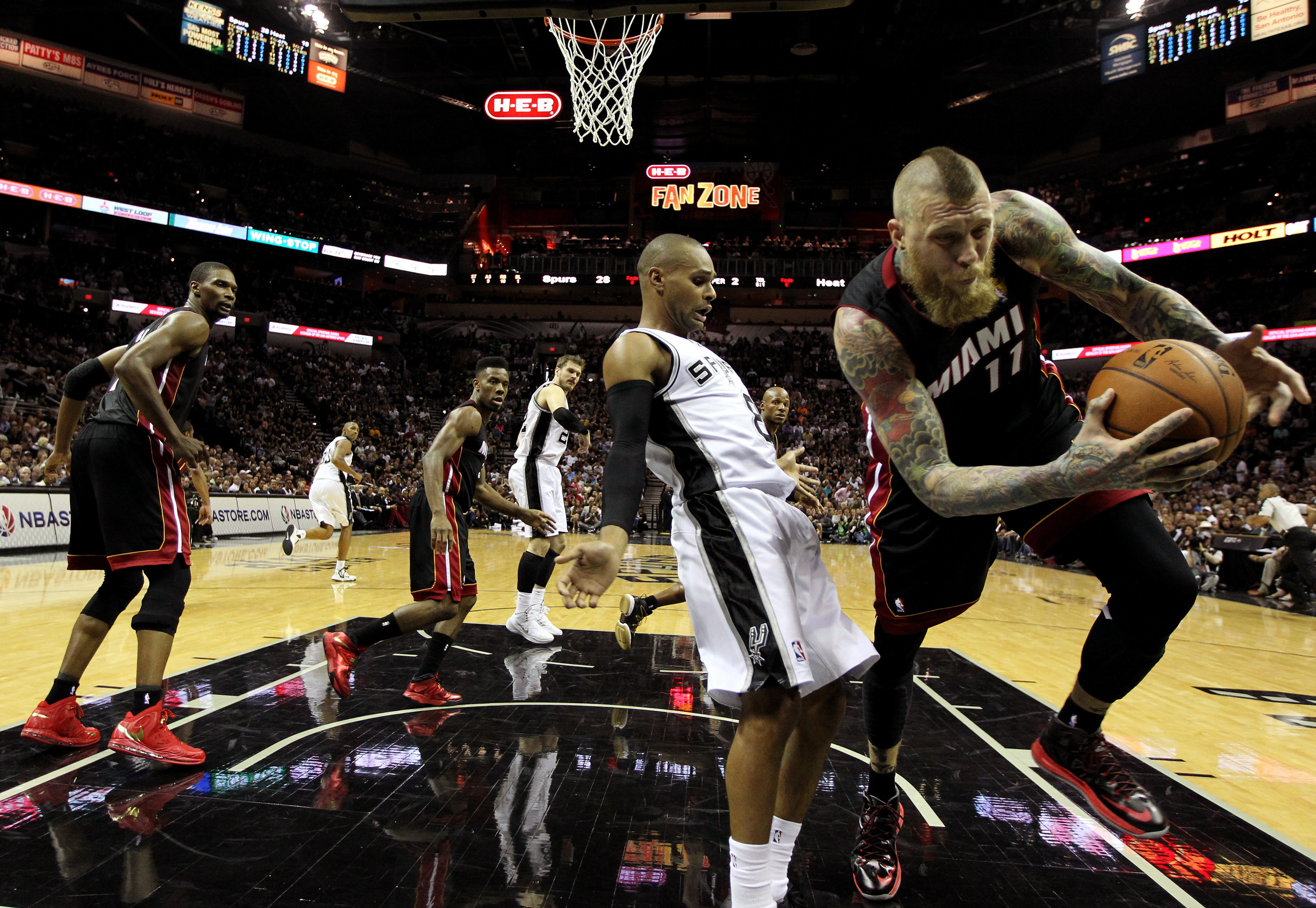 Patty Mills #8 of the San Antonio Spurs and Chris Andersen #11 of the Miami Heat battle for a loose ball during Game 2 of the 2014 NBA Finals in San Antonio on June 8, 2014.