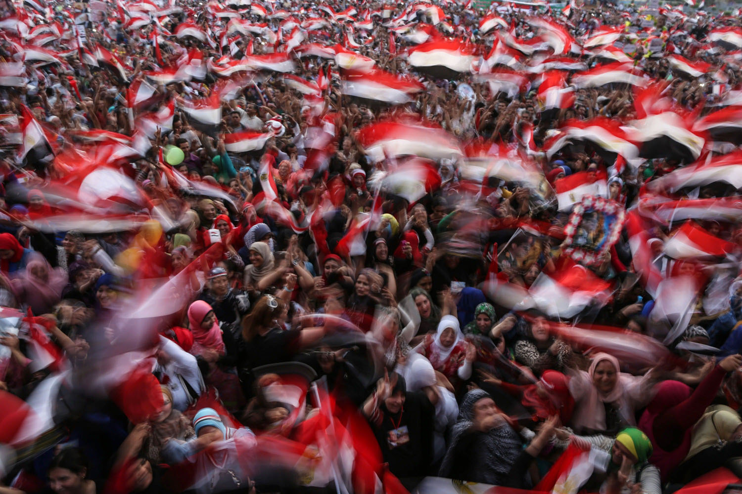 June 3, 2014. Egyptians wave national flags as they celebrate in Cairo's Tahrir Square after ex-army chief Abdel Fattah al-Sisi won 96.9 percent of votes in Egypt's presidential election.