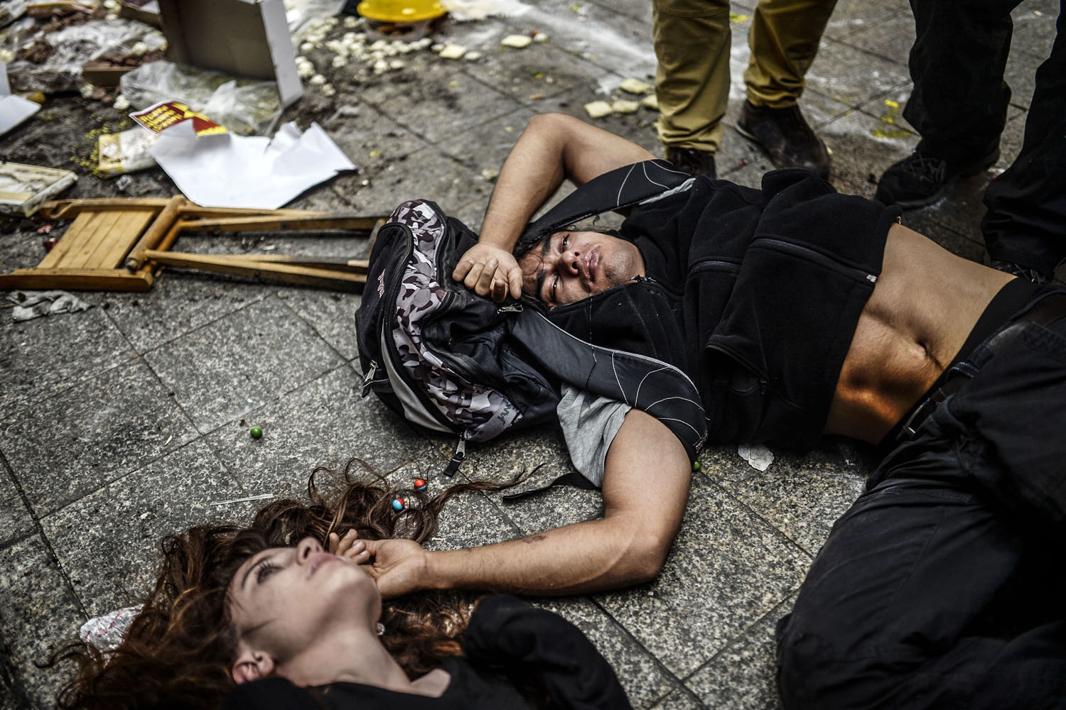 May 31, 2014. Injured protesters lie on the ground as Turkish riot police officers fire tear gas to disperse demonstrators gathered on the central Istoklal avenue near Taksim square in Istanbul.