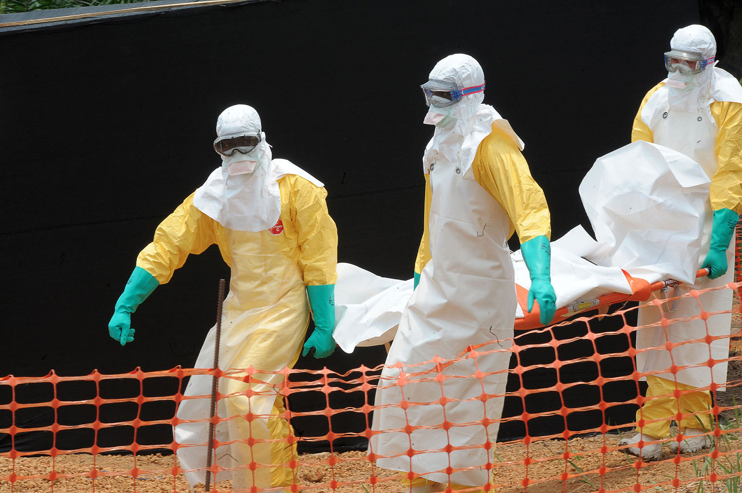 Doctors Without Borders staff carrying the body of a person killed by viral hemorrhagic fever at a center for victims of the Ebola virus in Gueckedou on April 1, 2014.