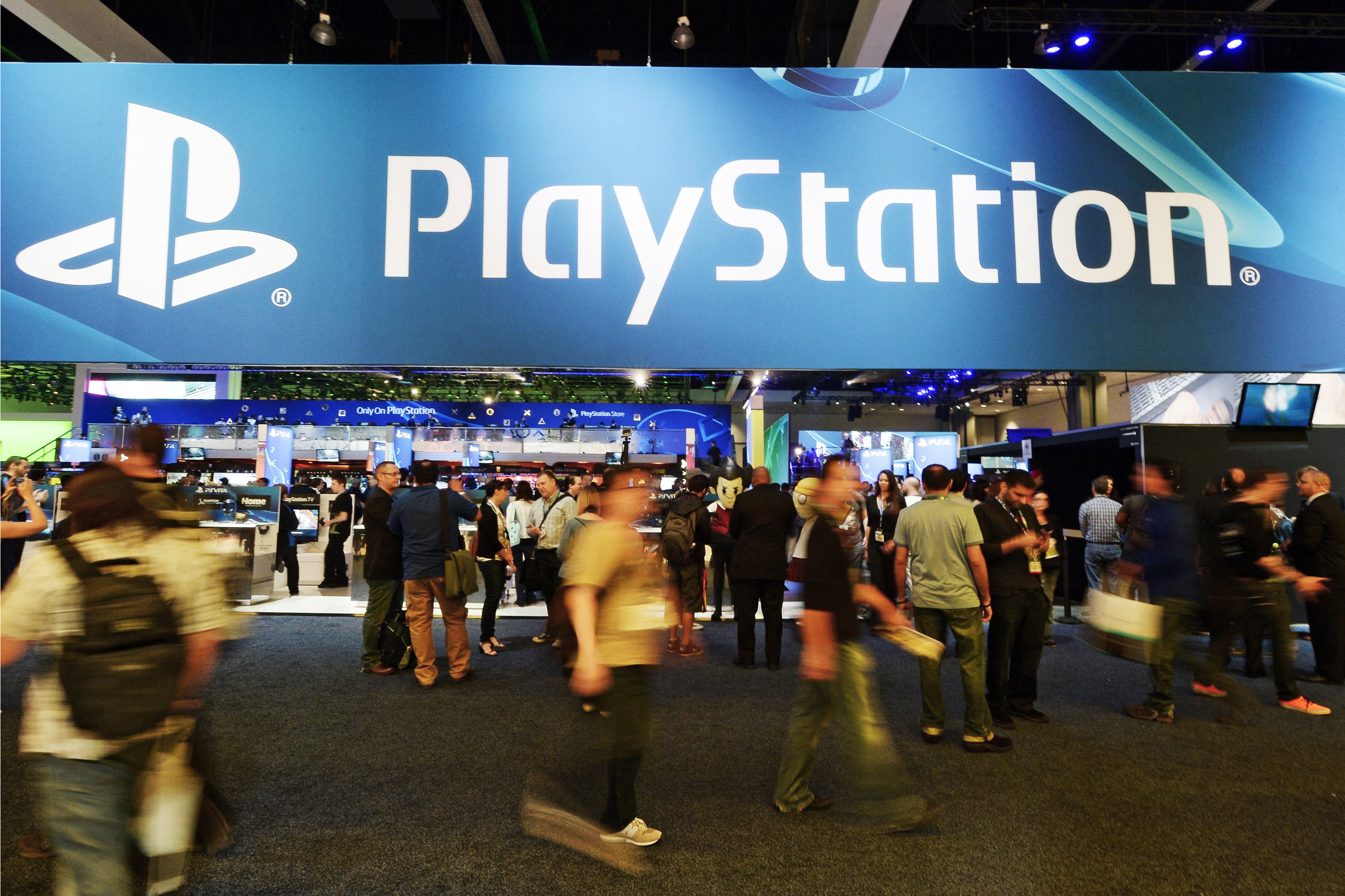 Attendees walk past the Sony Playstation booth at the 2014 Electronic Entertainment Expo, known as E3, in Los Angeles on June 11, 2014.