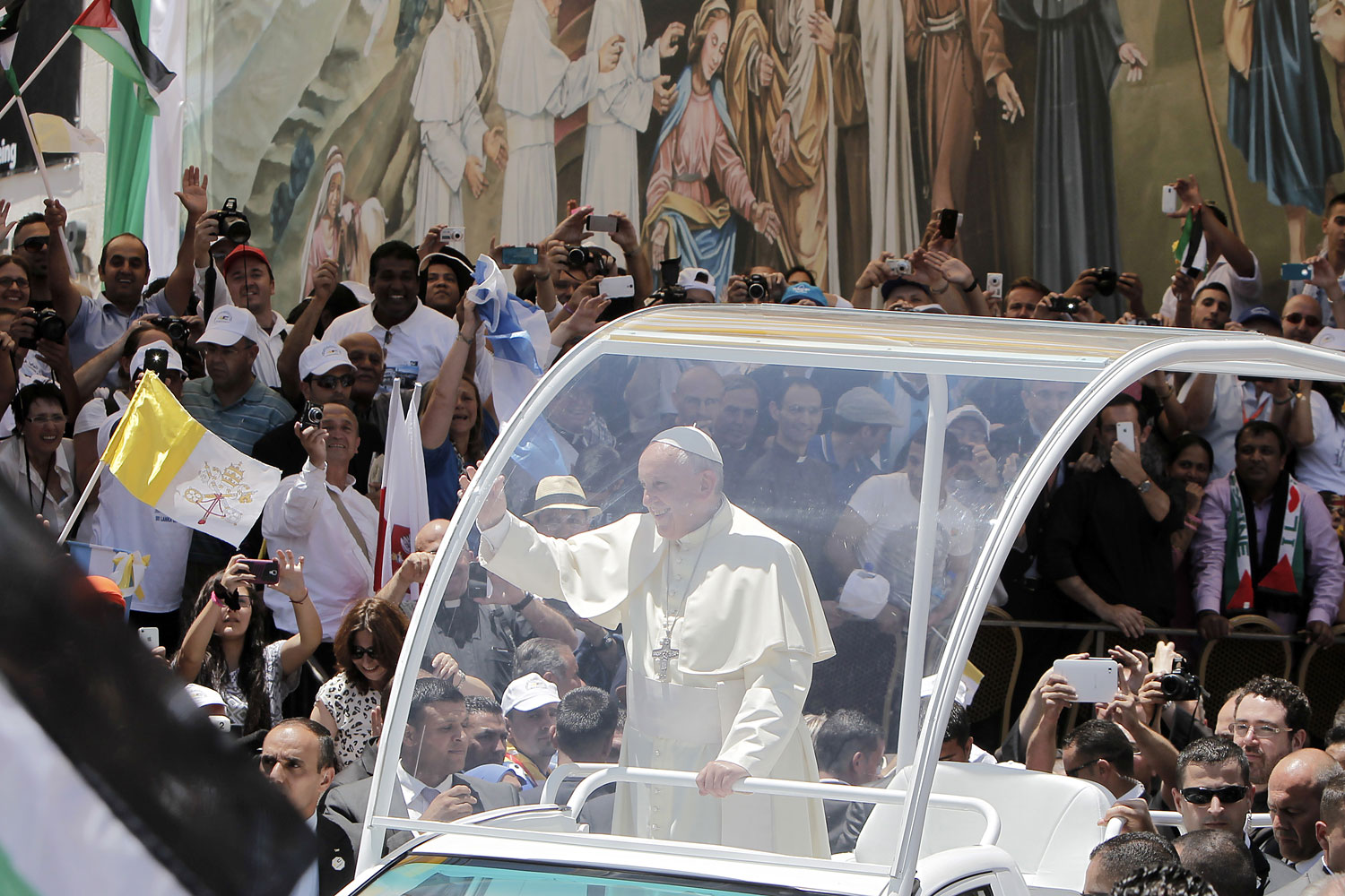 Pope Francis waves to the crowd, from his pope-mobile, as he leaves the Manger Square after presiding over an open-air mass on May 25, 2014, outside the Church of the Nativity in the West Bank Biblical town of Bethlehem.