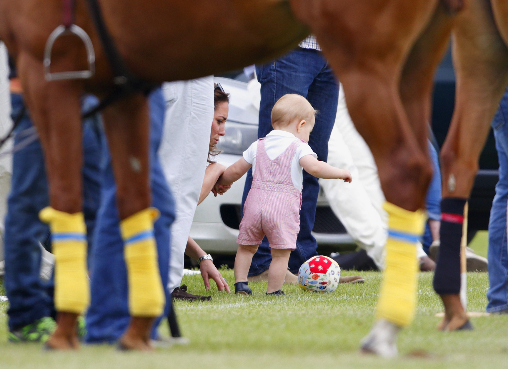Prince George of Cambridge plays with a football whilst holding his mother Catherine, Duchess of Cambridge's hand at Cirencester Park Polo Club on June 15, 2014 in Cirencester, England.
