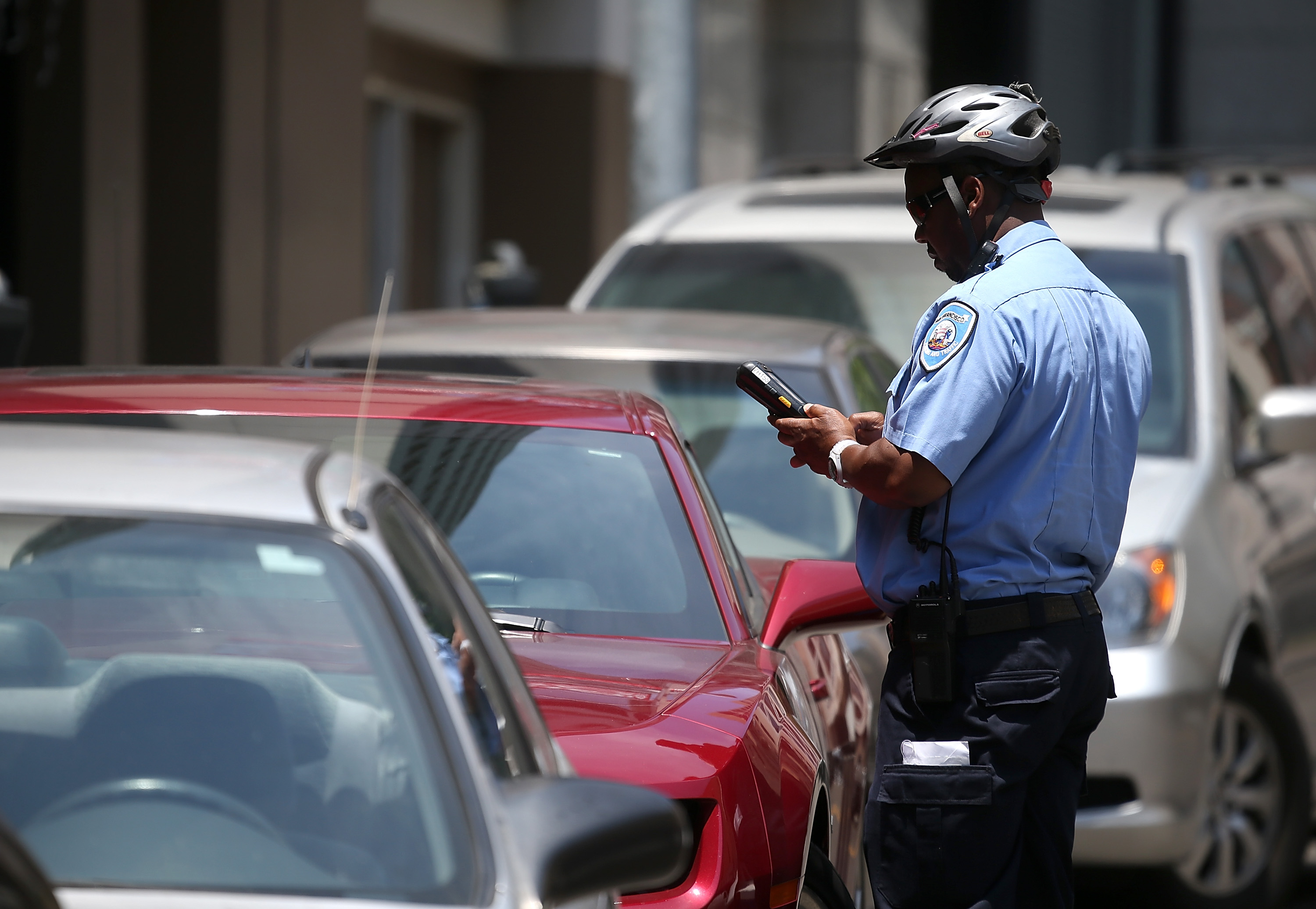 A San Francisco Municipal Transportation Agency parking control officer writes a parking ticket for an illegally parked car on July 3, 2013 in San Francisco.