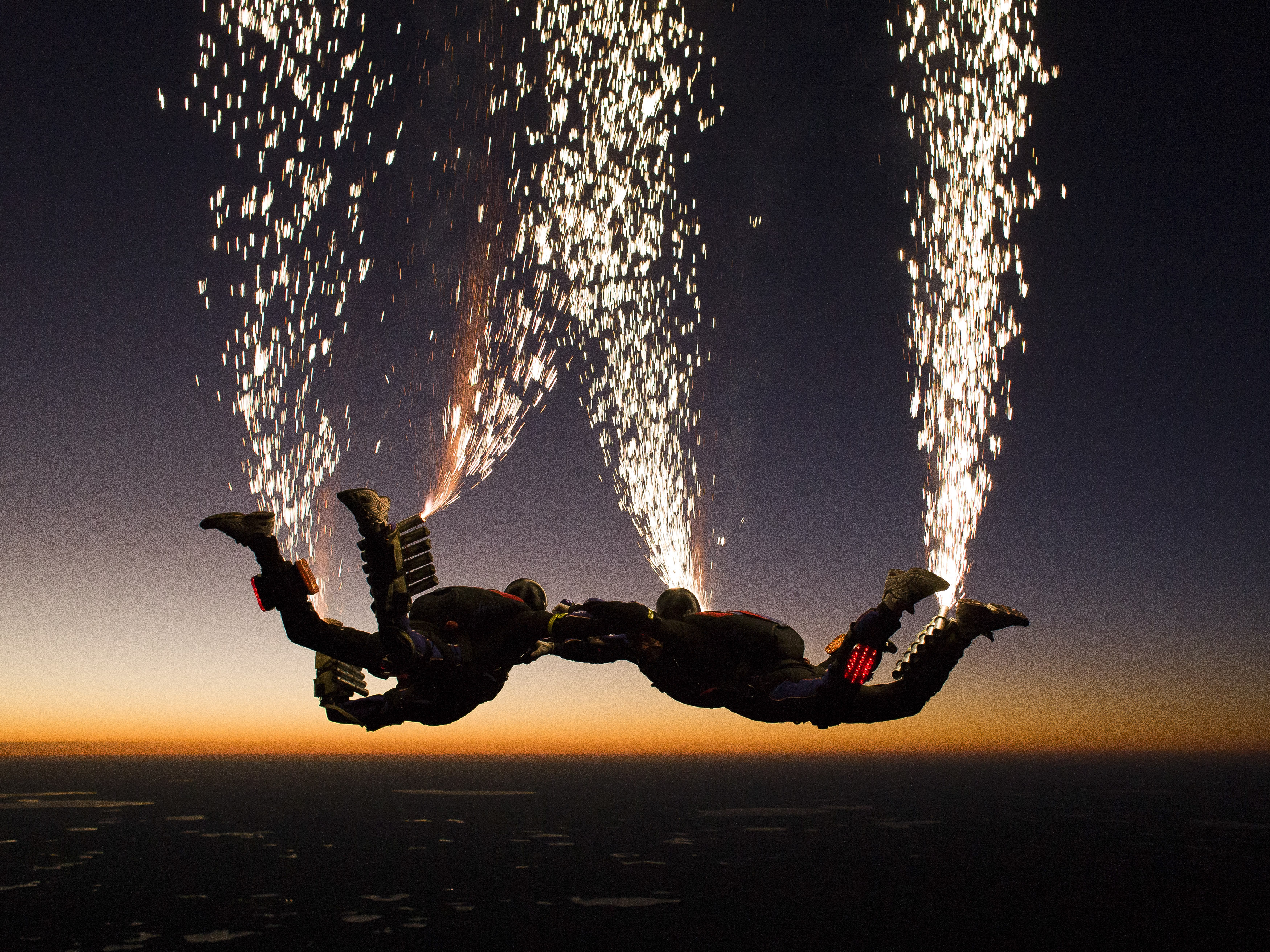 The Fastrax skydiving team set off fireworks as they jump out of the plane.