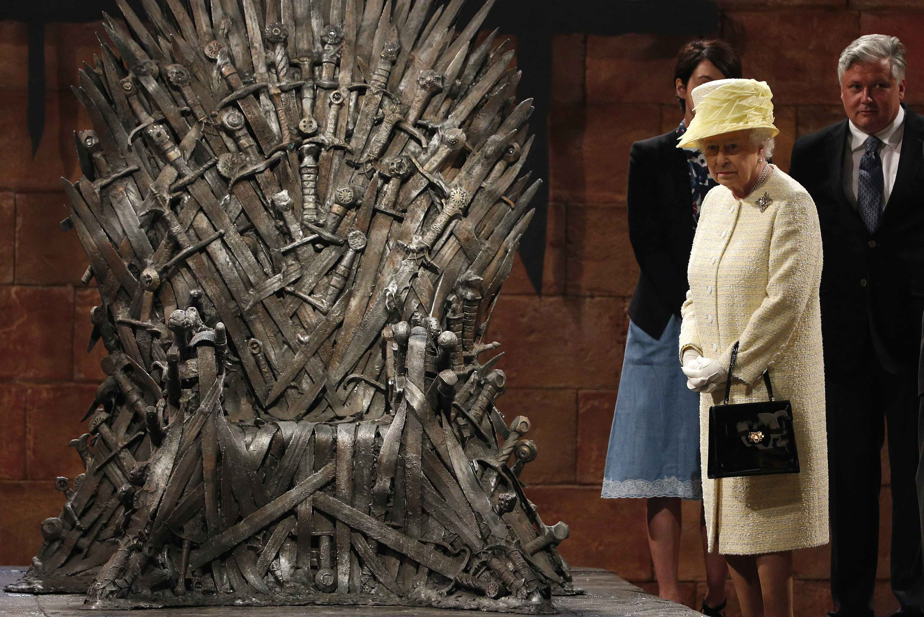 Britain's Queen Elizabeth looks at the Iron Throne as she meets members of the cast on the set of the television show Game of Thrones in the Titanic Quarter of Belfast, Northern Ireland, June 24, 2014.