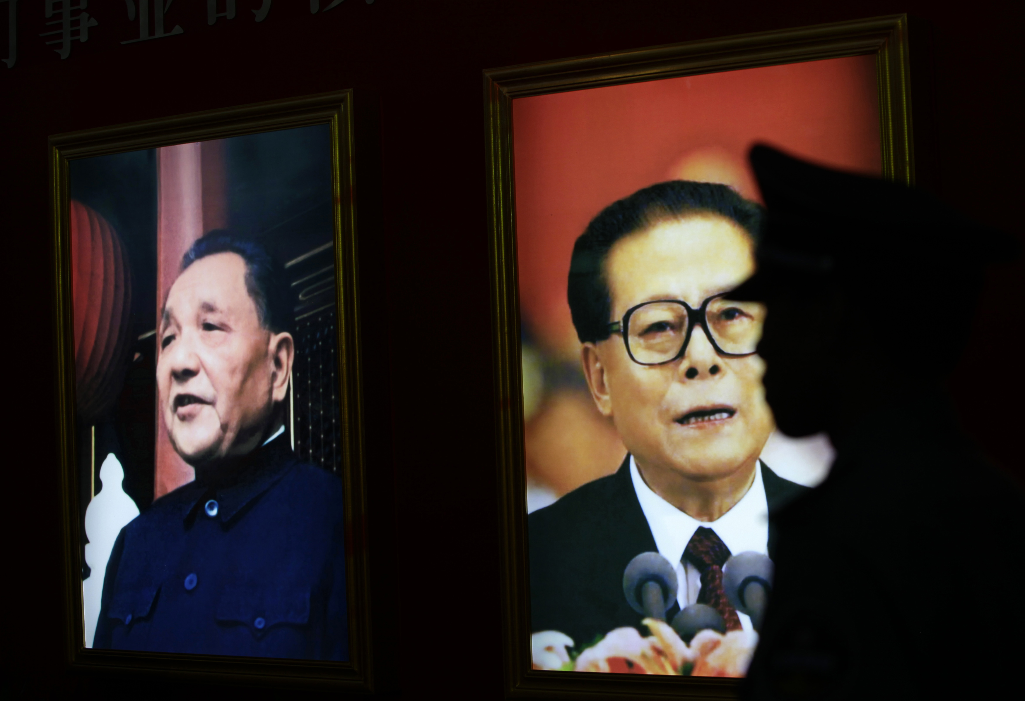 A security guard stands next to the pictures of China's former President Jiang Zemin, right, and late paramount leader Deng Xiaoping at an exhibition to celebrate the 90th anniversary of the founding of the Chinese Communist Party in 2011