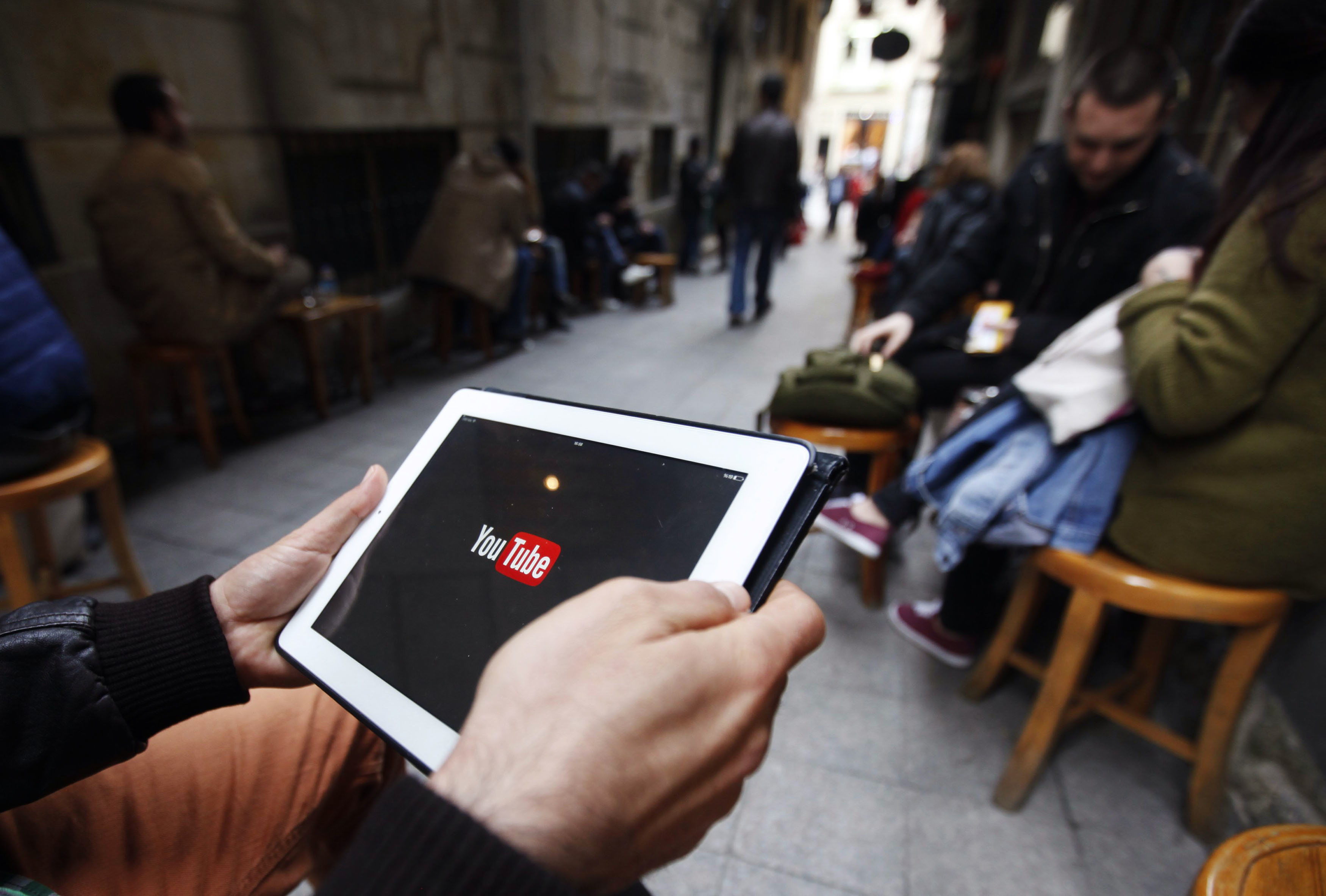 A man tries to connect to YouTube with his tablet at a café in Istanbul on March 27, 2014.