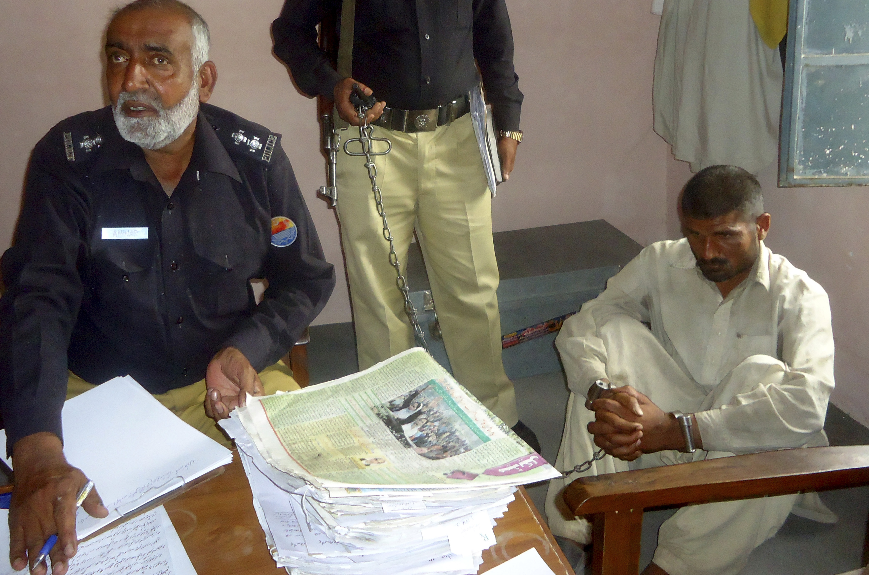 Mohammad Arif Ali, 35, right, sits in custody at a police station in the town of Darya Khan in Bhakkar district, Pakistan's Punjab province, on April 14, 2014.