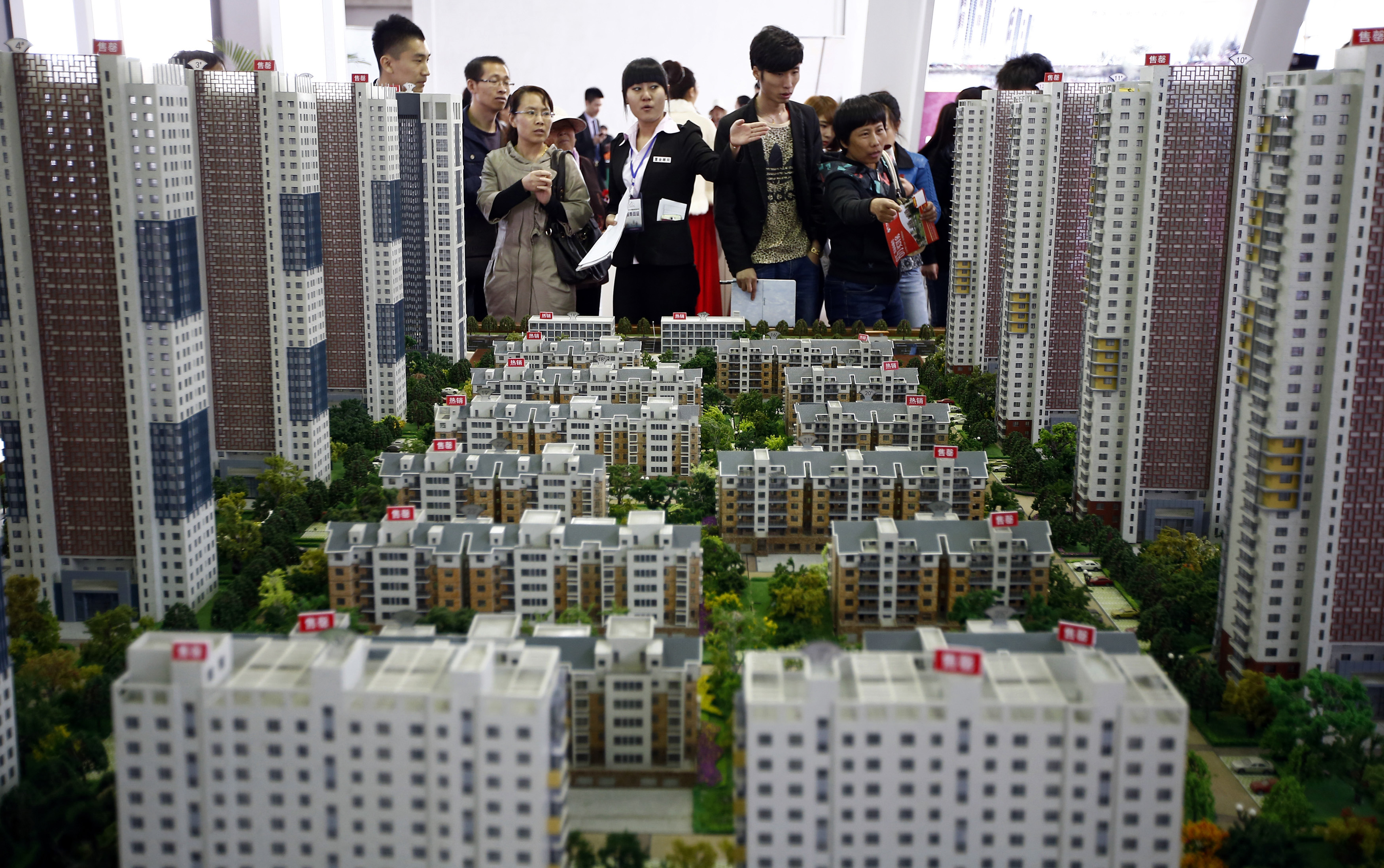 A sales assistant talks to visitors in front of models of apartments at a real estate exhibition in Shenyang, Liaoning province April 17, 2014.