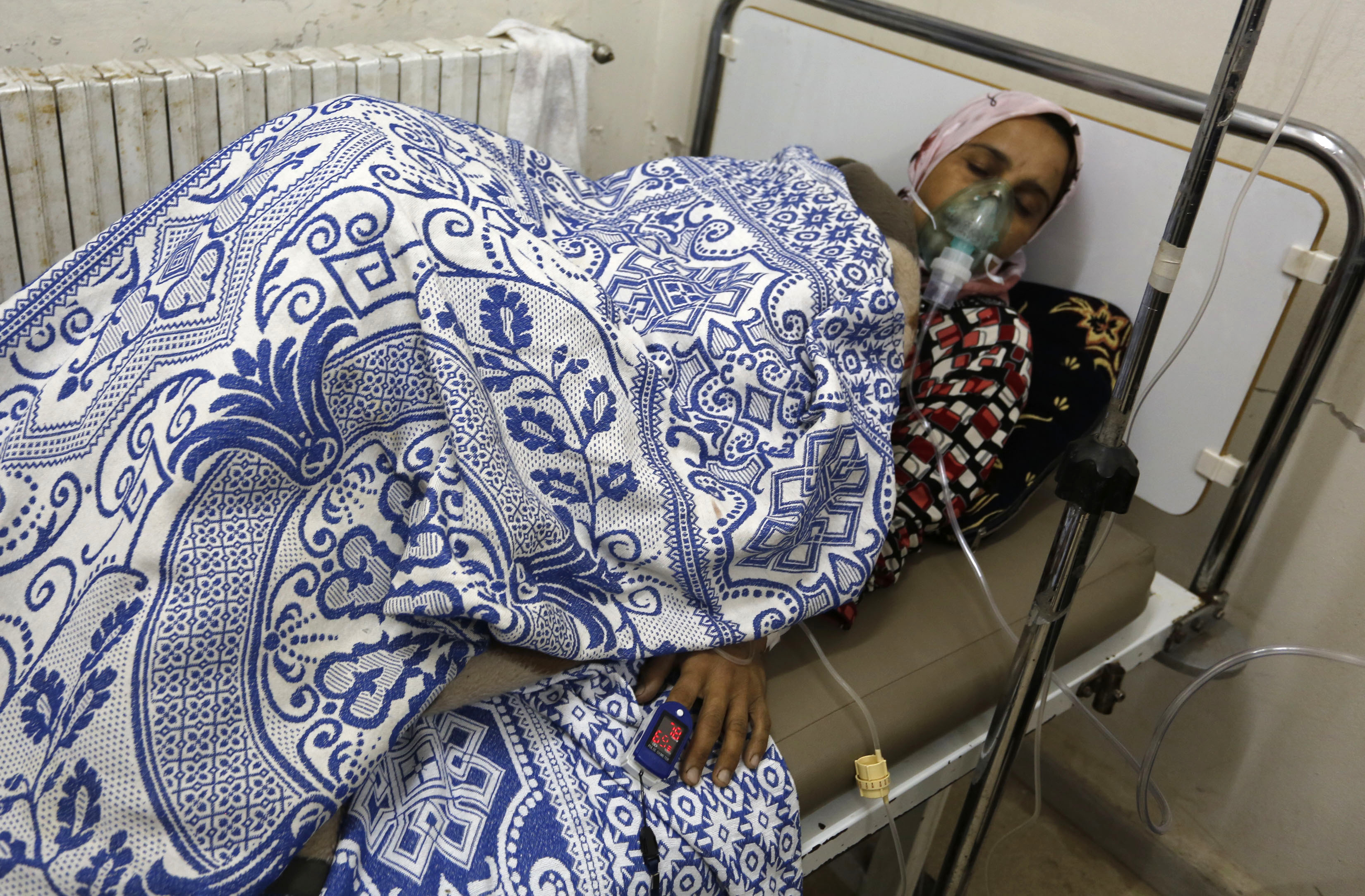 A woman, affected by what activists say was a gas attack, receives treatment inside a makeshift hospital in Kfar Zeita village in the central Syria province of Hama on May 22, 2014.