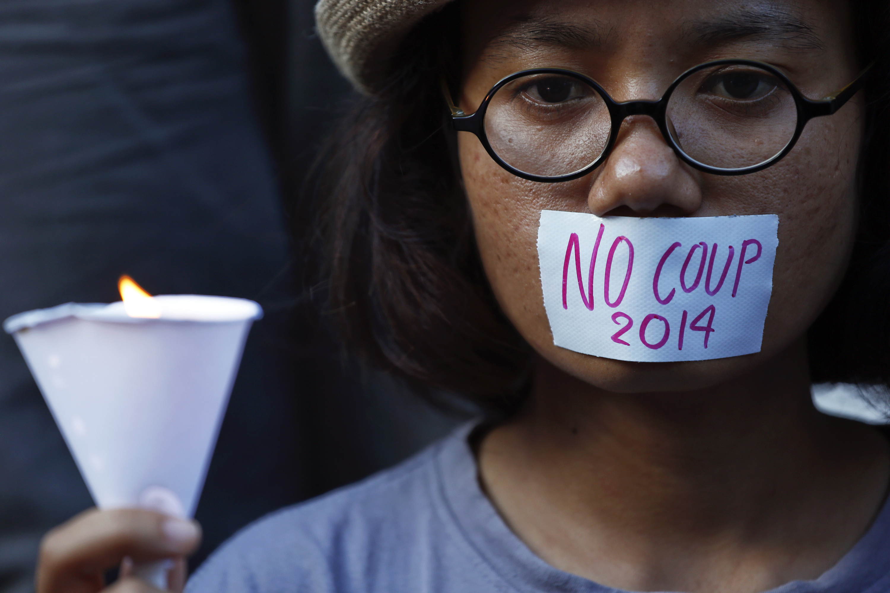A girl holds a candle during a protest against military rule in central Bangkok, a day after Thai army chief seized power in a coup May 23, 2014.