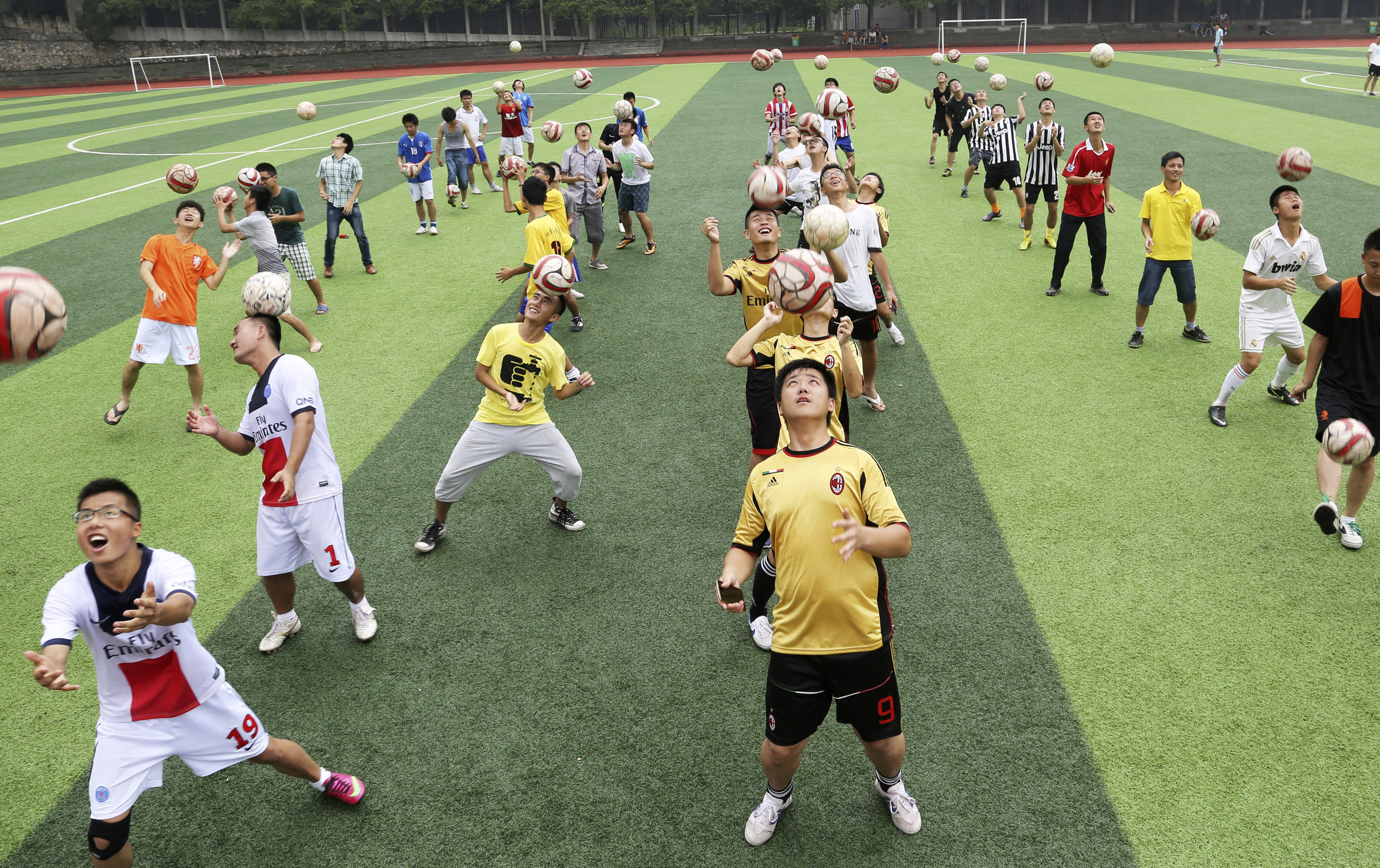 Students head soccer balls during a competition at the campus of University of South China in Hengyang, Hunan province, June 3, 2014.