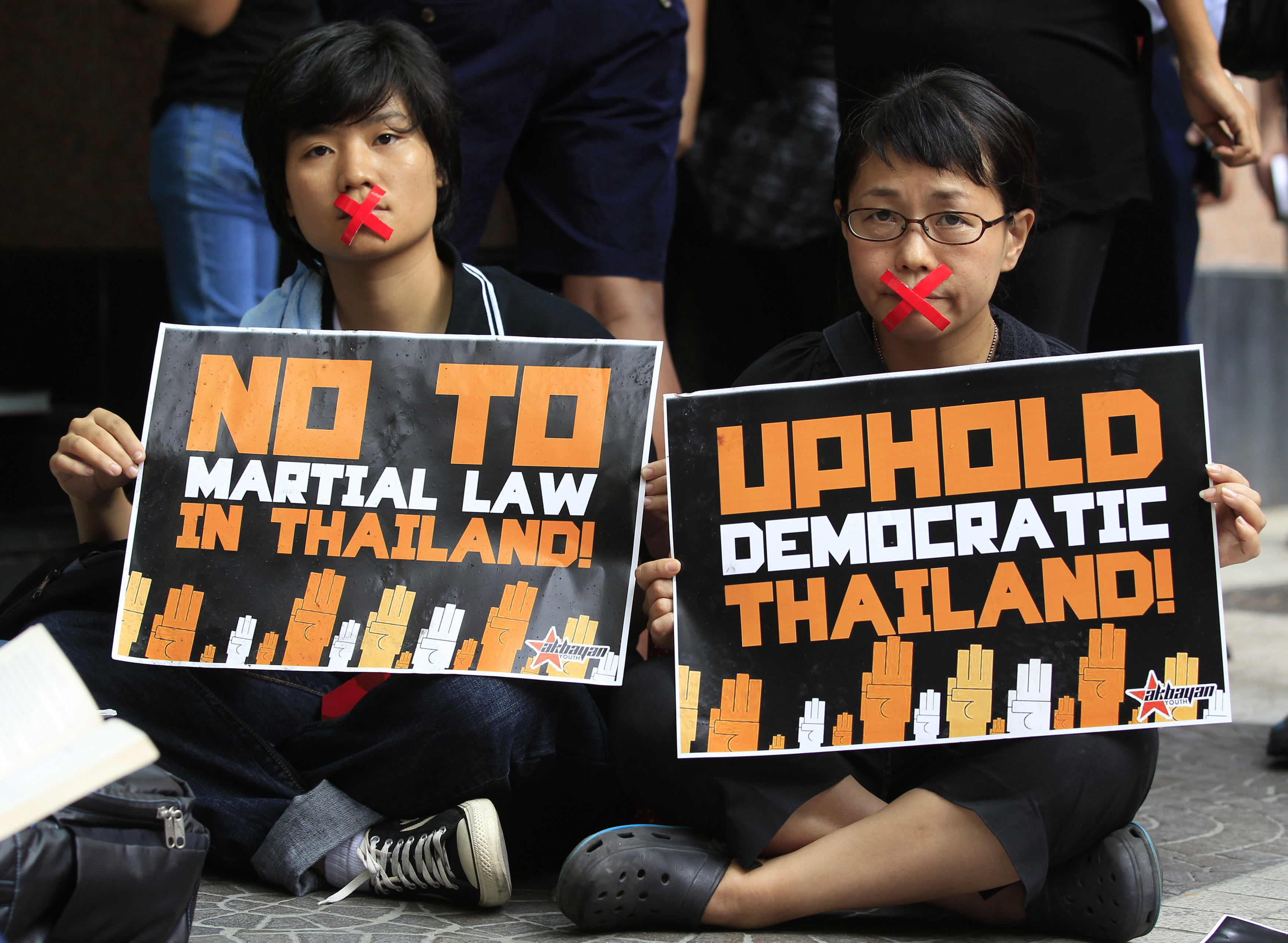 Activists, with their mouths taped up as a form of protest against the ongoing military rule in Thailand, hold placards during a picket in front of the Thai embassy in Manila  on June 5, 2014