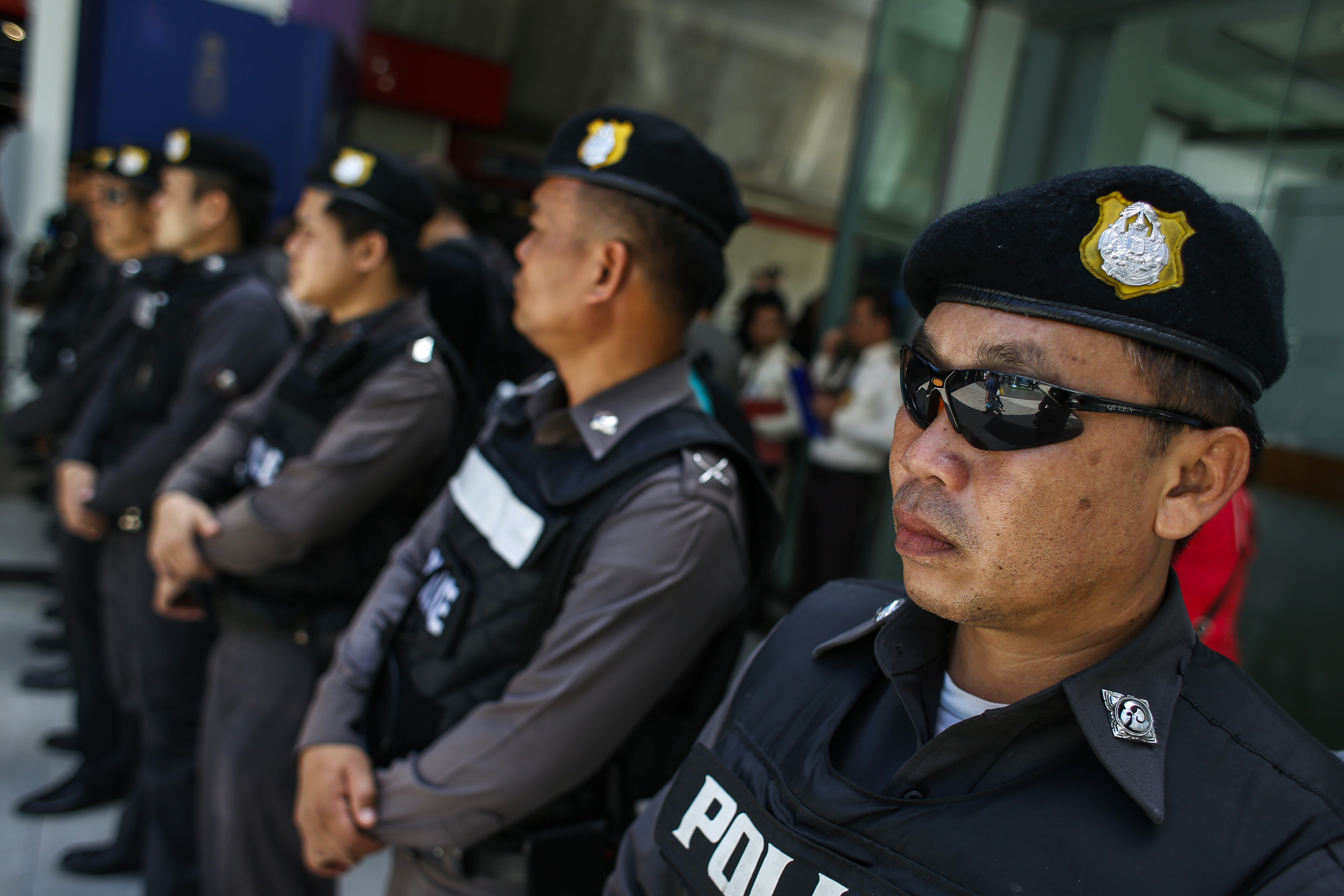 Police officers stand guard at a shopping mall in Bangkok on June 8, 2014