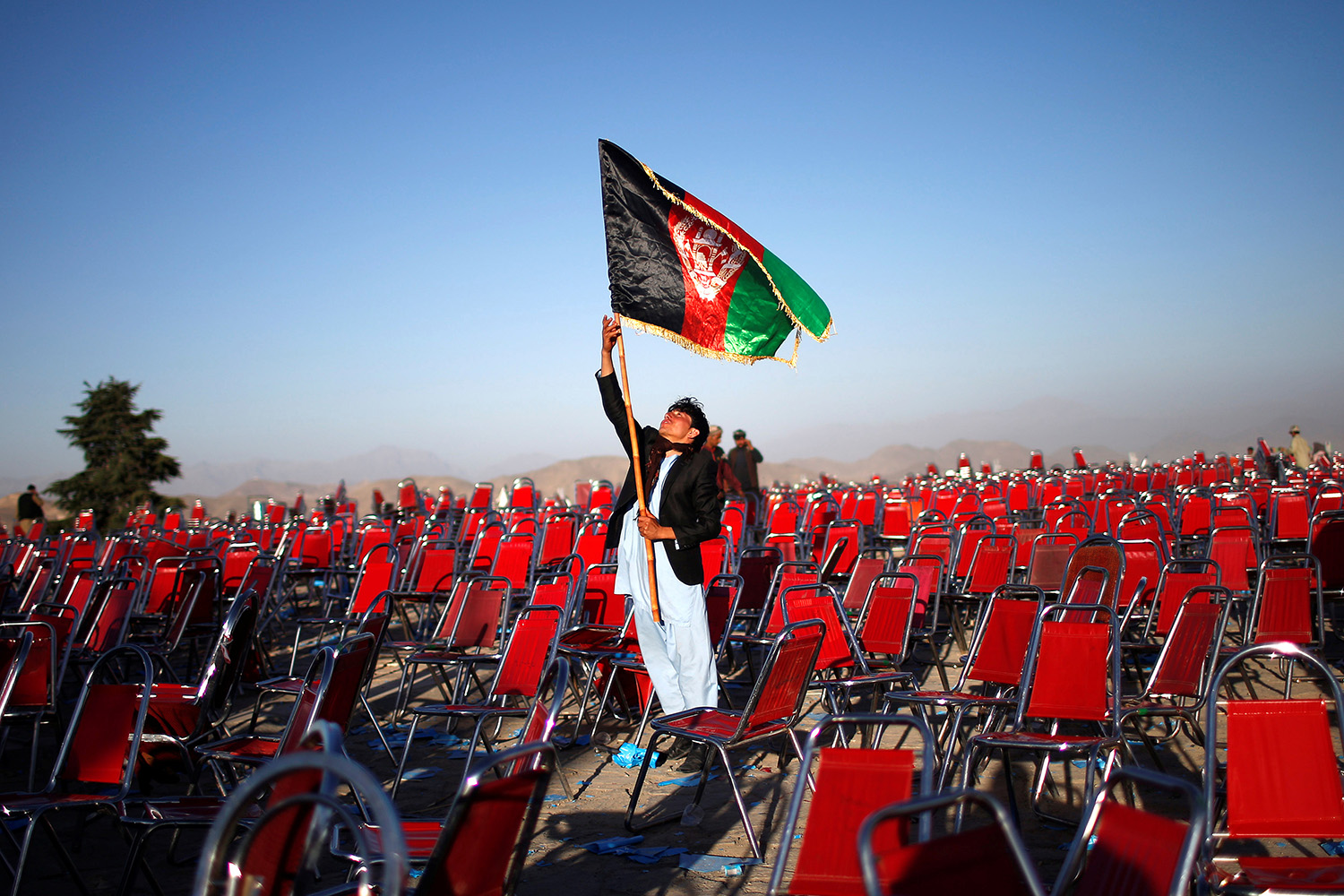 June 9, 2014. A supporter of Afghan presidential candidate Abdullah Abdullah holds an Afghan flag after an election campaign rally in Paghman district of Kabul.