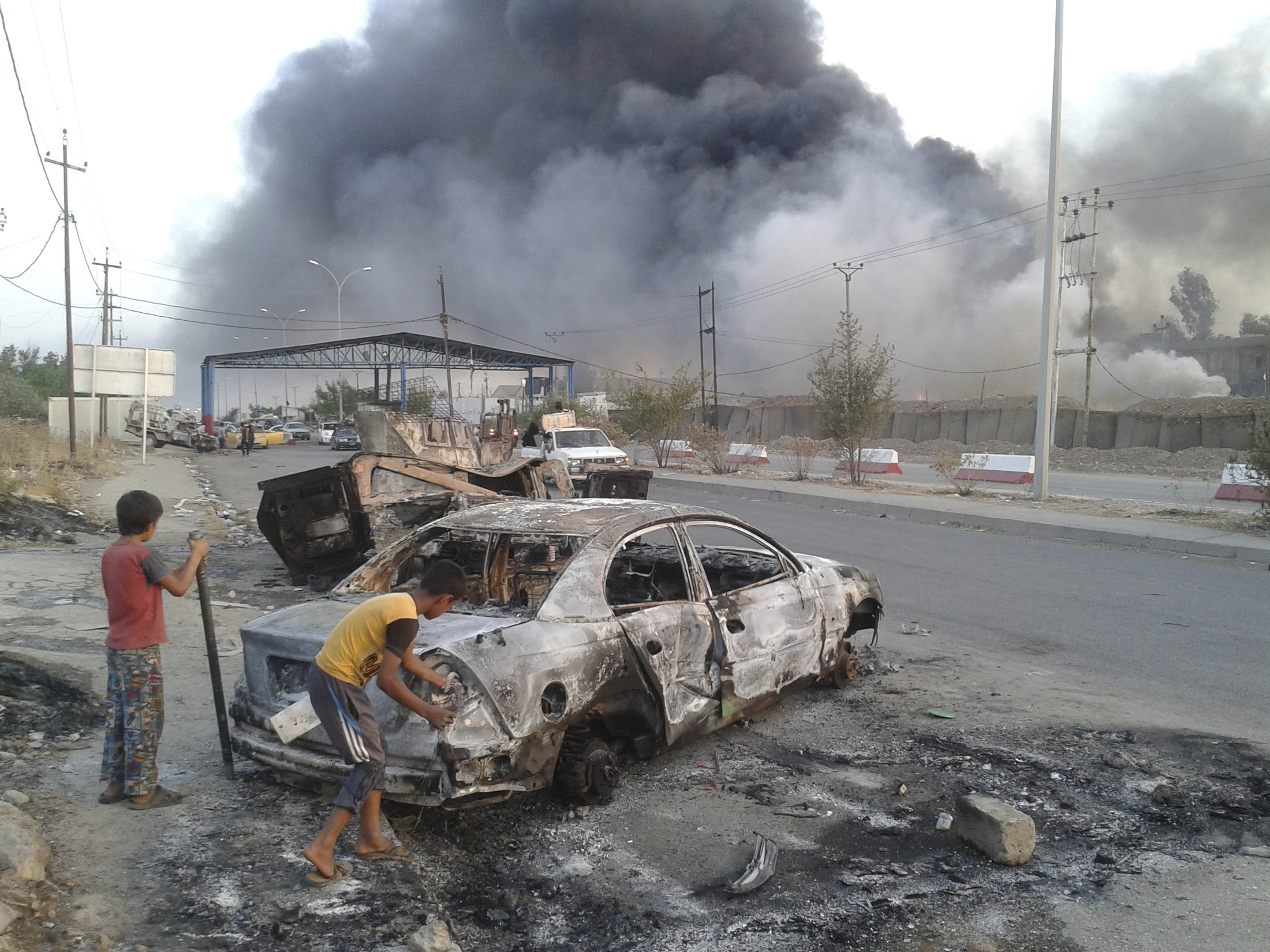 Children stand next to a burned-out vehicle during clashes between Iraqi forces and the Islamic State of Iraq and Syria in the northern Iraqi city of Mosul on June 10.