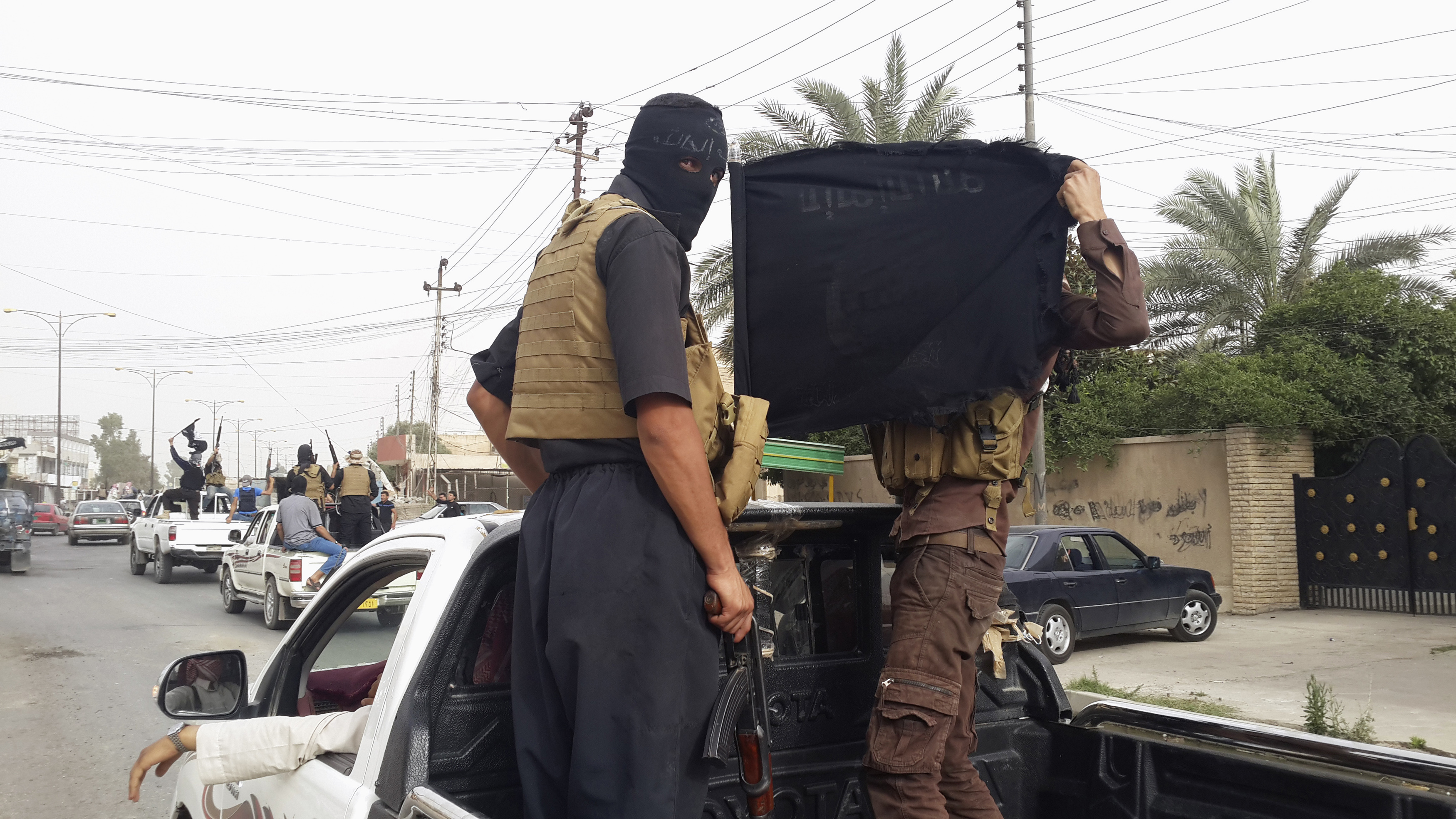 Fighters of the Islamic State of Iraq and the Levant (ISIL) celebrate on vehicles taken from Iraqi security forces, at a street in city of Mosul, June 12, 2014.