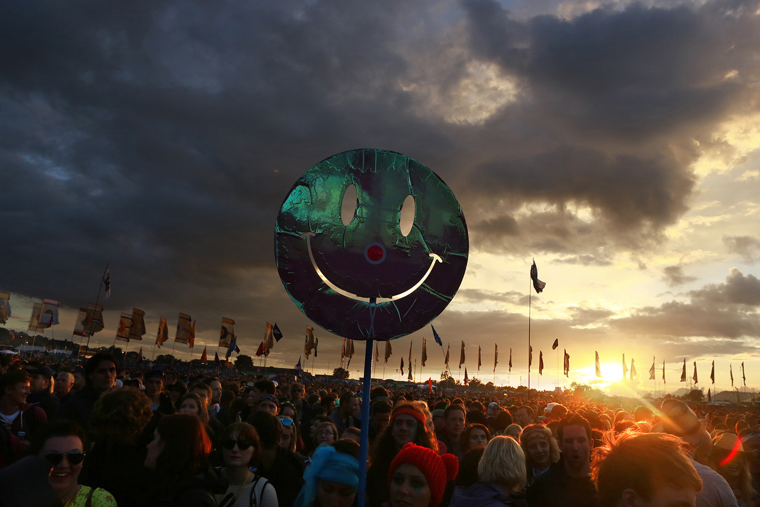June 27, 2014. A smiley face is held up by a festival-goer as the sun sets in front of the Other Stage at Worthy Farm in Somerset, England, during the Glastonbury Festival.