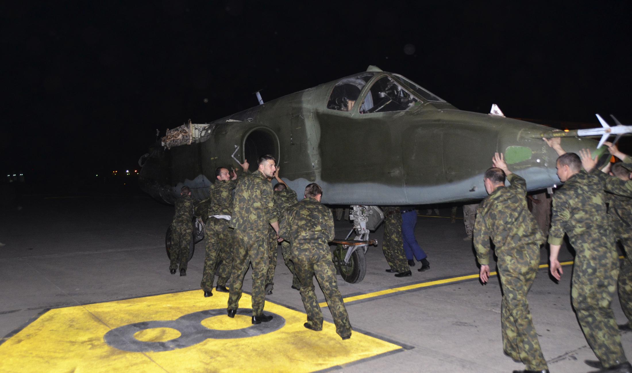 Russian troops unload a Russian Su-25 attack plane in Baghdad on Saturday.