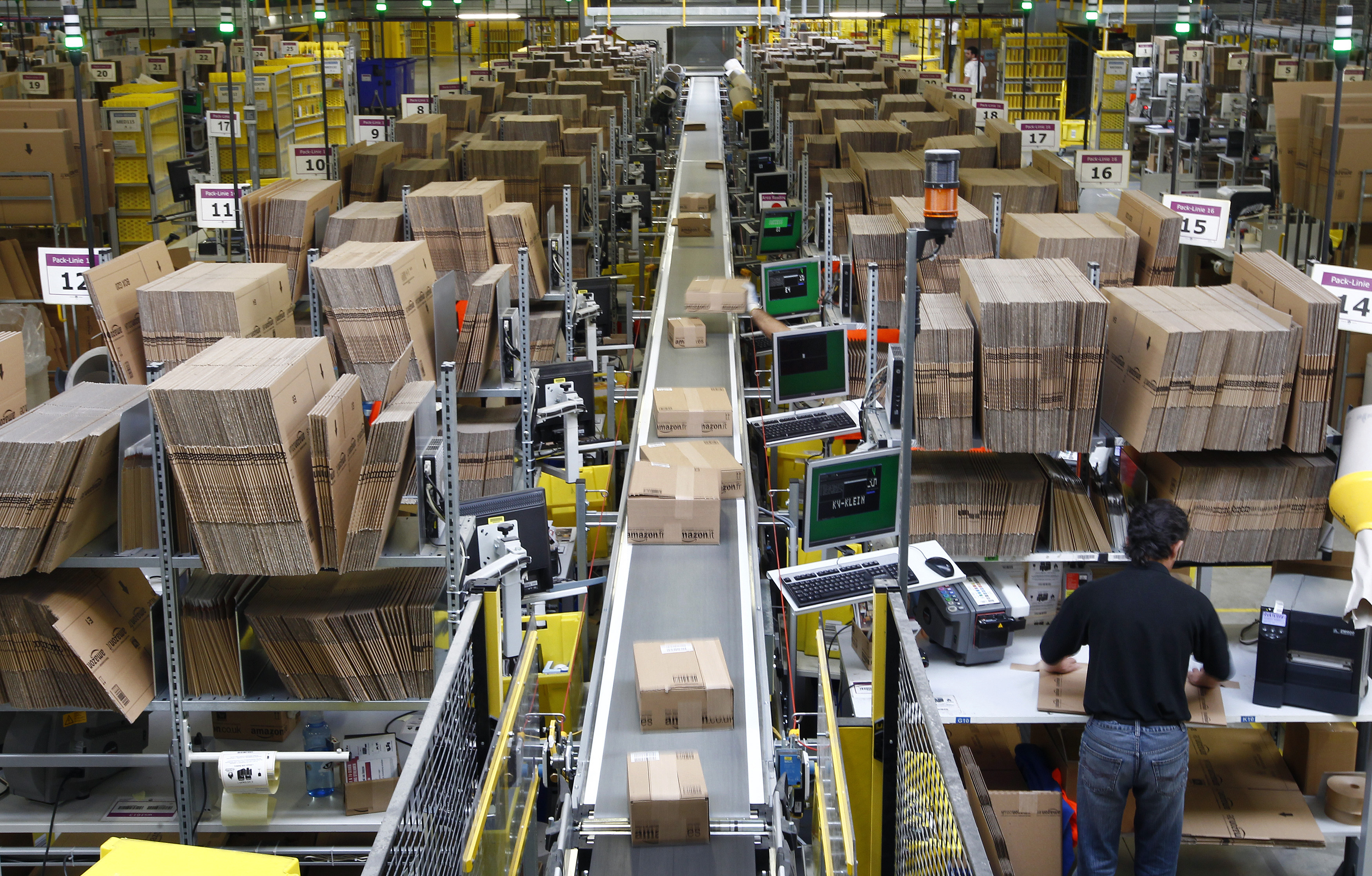 Workers pack boxes at Amazon's logistics center in Graben, Germany, on Dec. 16, 2013