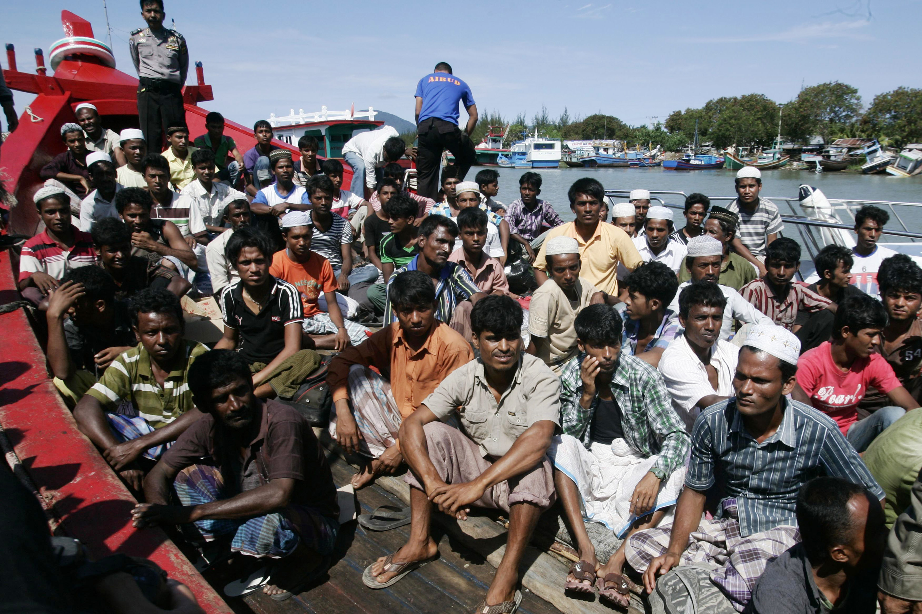 Ethnic Rohingya refugees from Burma sit on a wooden boat as they wait for transportation to a temporary shelter in Aceh Besar after arriving at Lampulo habour April 8, 2013.
