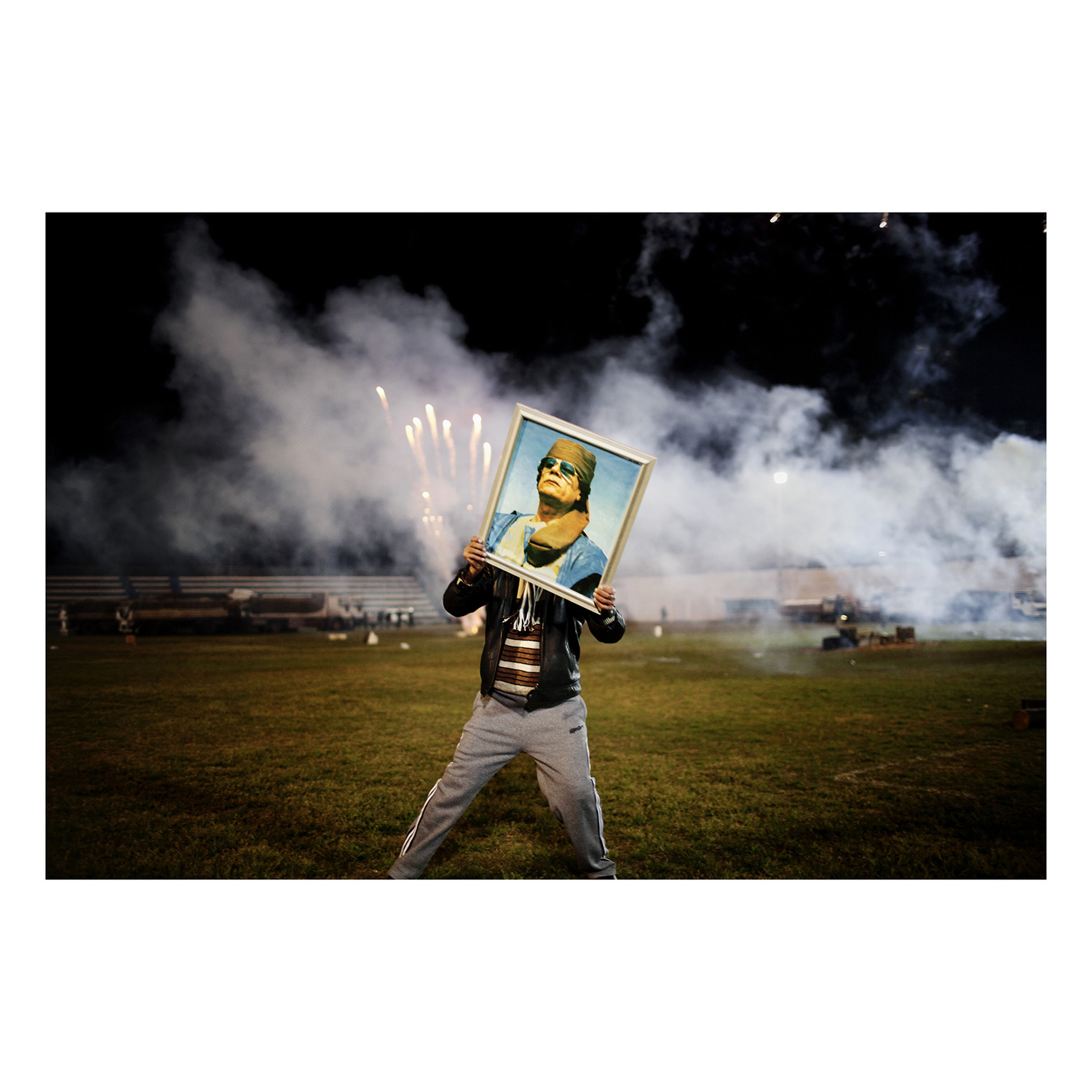 A Qaddafi supporter holds a portrait of the Libyan leader as fireworks go up in the background on a soccer field in a suburb of Zawiyah where government minders took a group of foreign journalists to attend a staged celebration. Libya. 2011.