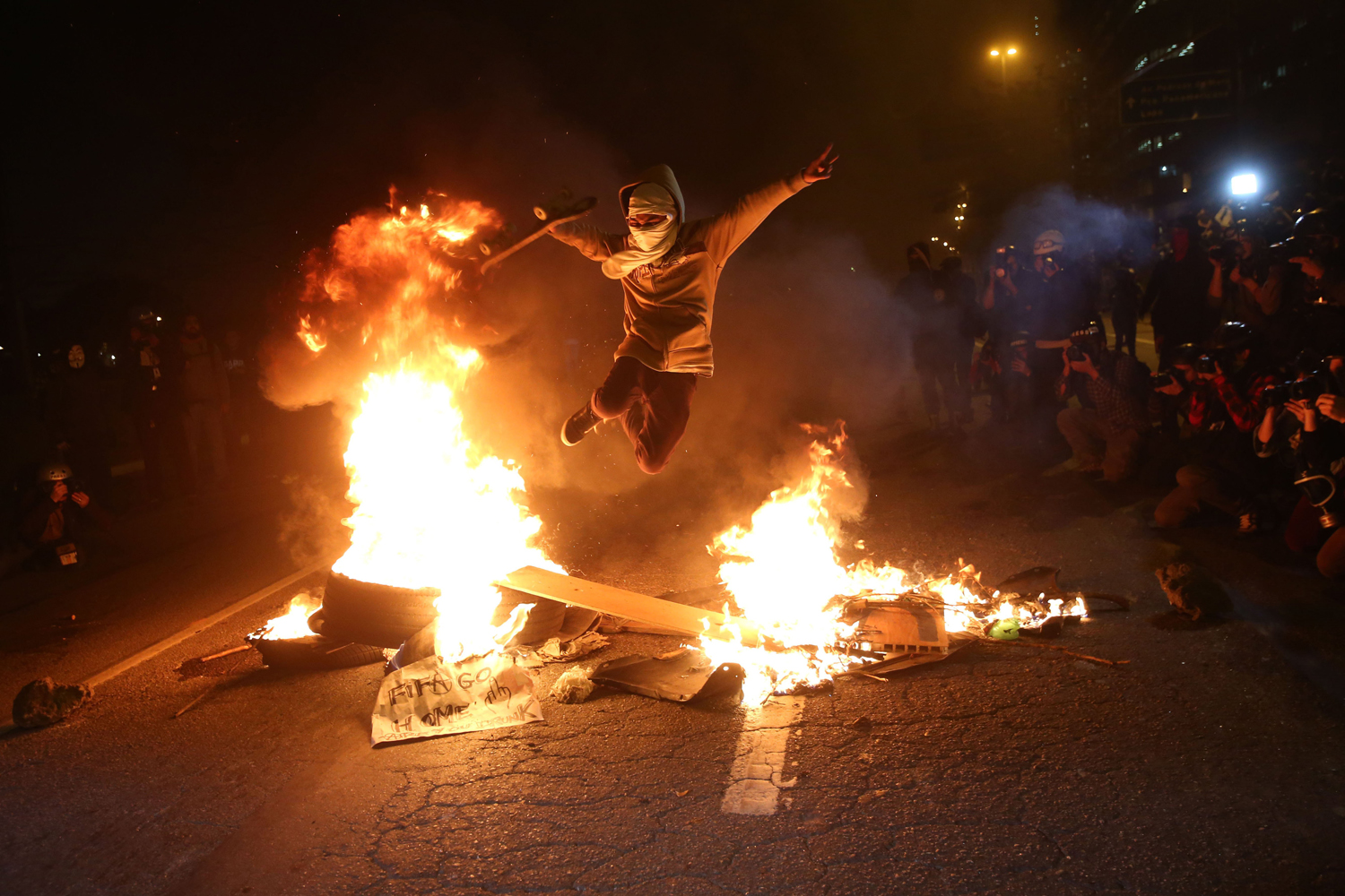 A protester jumps over a fire barricade during a protest against 2014 FIFA World Cup in Sao Paulo, on June 19, 2014.