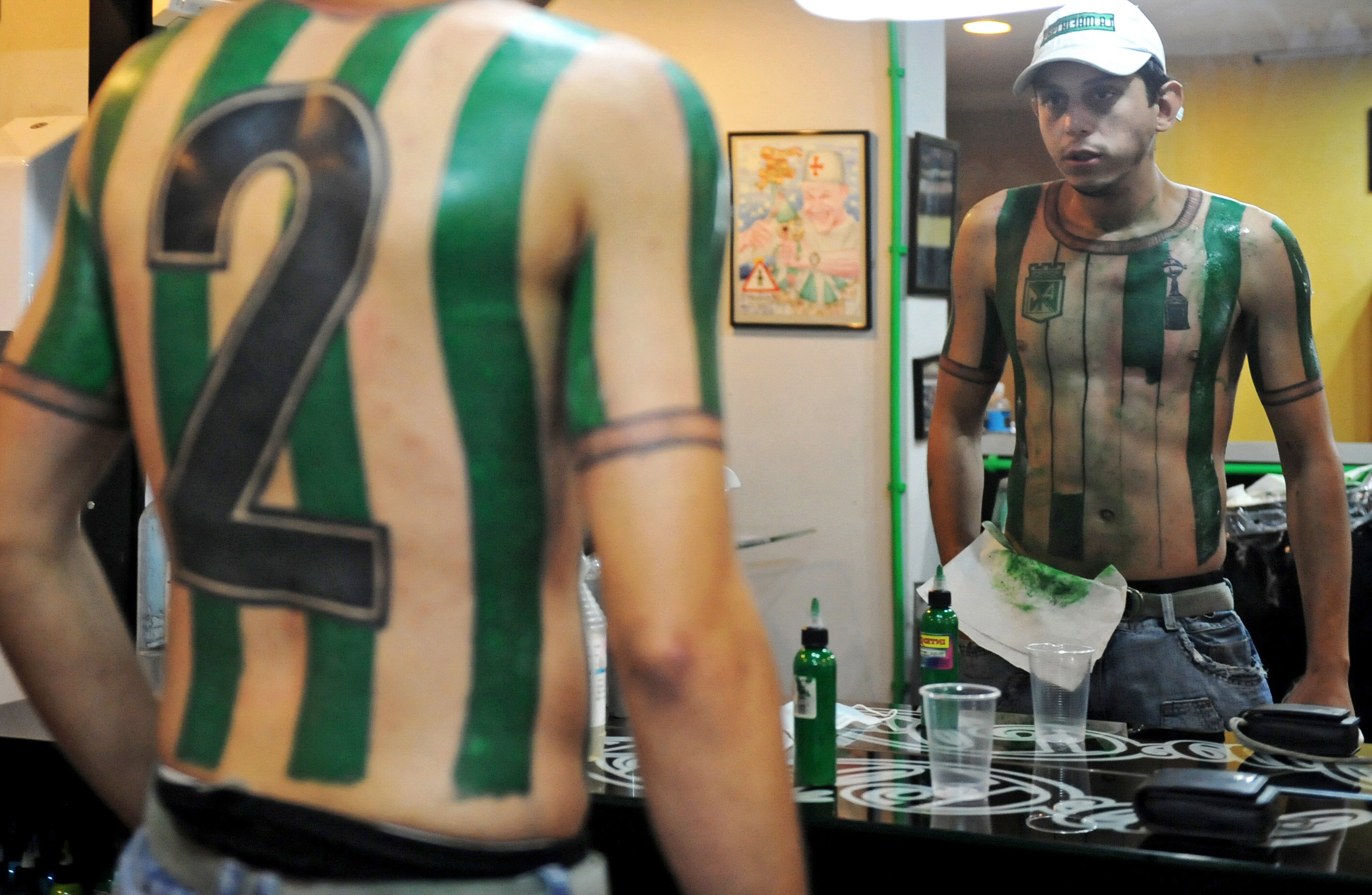 Colombian soccer fan Felipe Alvarez looks at his partially completed Atletico Nacional jersey tattoo in Medellin, Colombia on October 9, 2010.