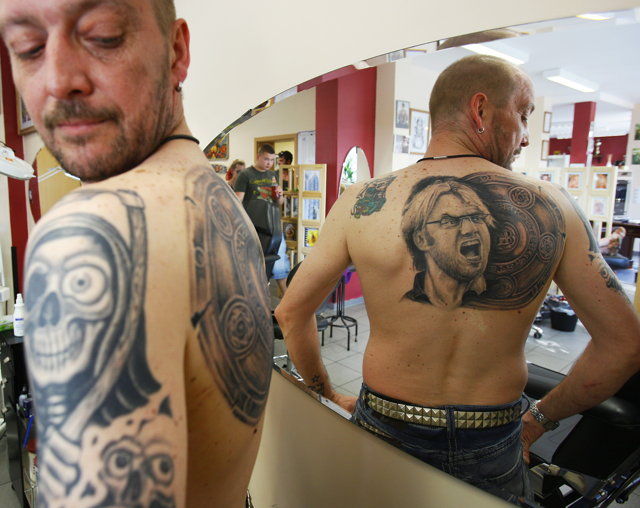 Soccer fan Martin Hueschen admires his new tattoo of Germany's soccer trophy and Borussia Dortmund soccer club's coach Juergen Klopp, at a tattoo shop in Unna, Germany on April 20, 2011.