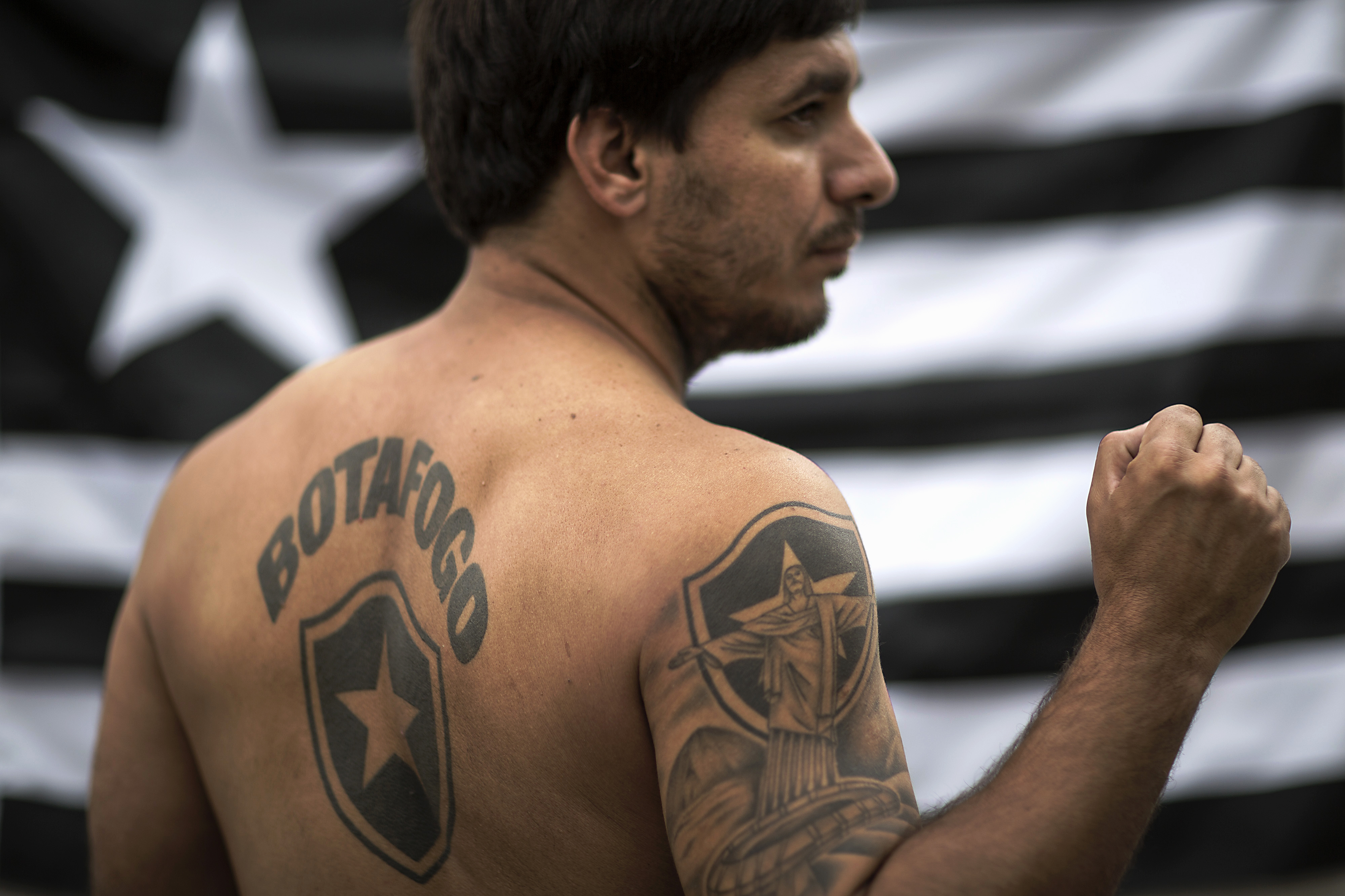 Carlos Eduardo poses for a photo showing his Botafogo's tattoos in Petropolis, Brazil on May 17, 2014.