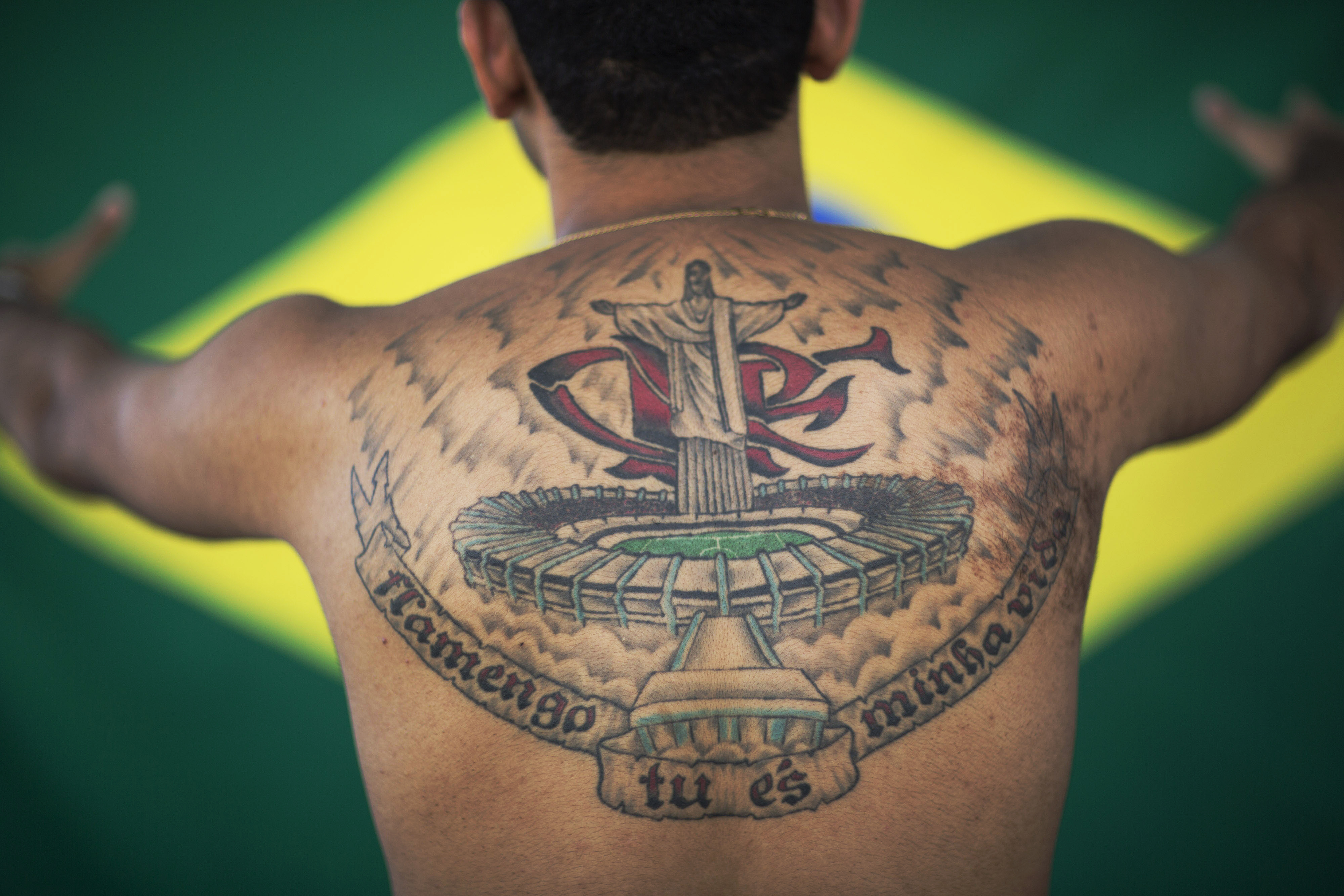 Felipe da Costa Almeida poses for a photo showing his tattoo of the Christ Redeemer statue over the Maracana stadium, backgrounded by the Flamengo soccer club initials in Rio de Janeiro, Brazil on May 30, 2014.