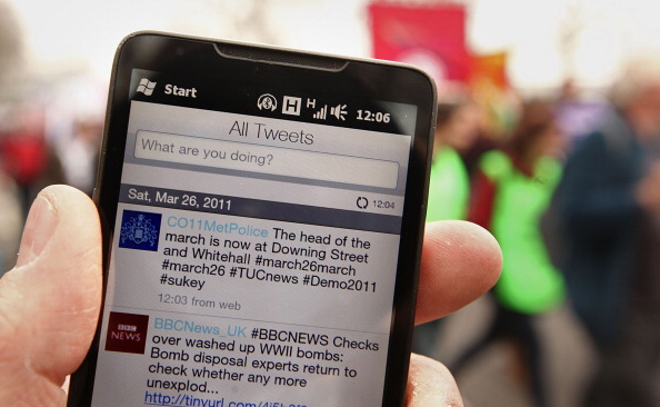 A smartphone displays the Metropolitan Police's Twitter feed during a 2011 protest against government guts in London. Companies are increasingly turning to monitoring social media to improve their businesses.