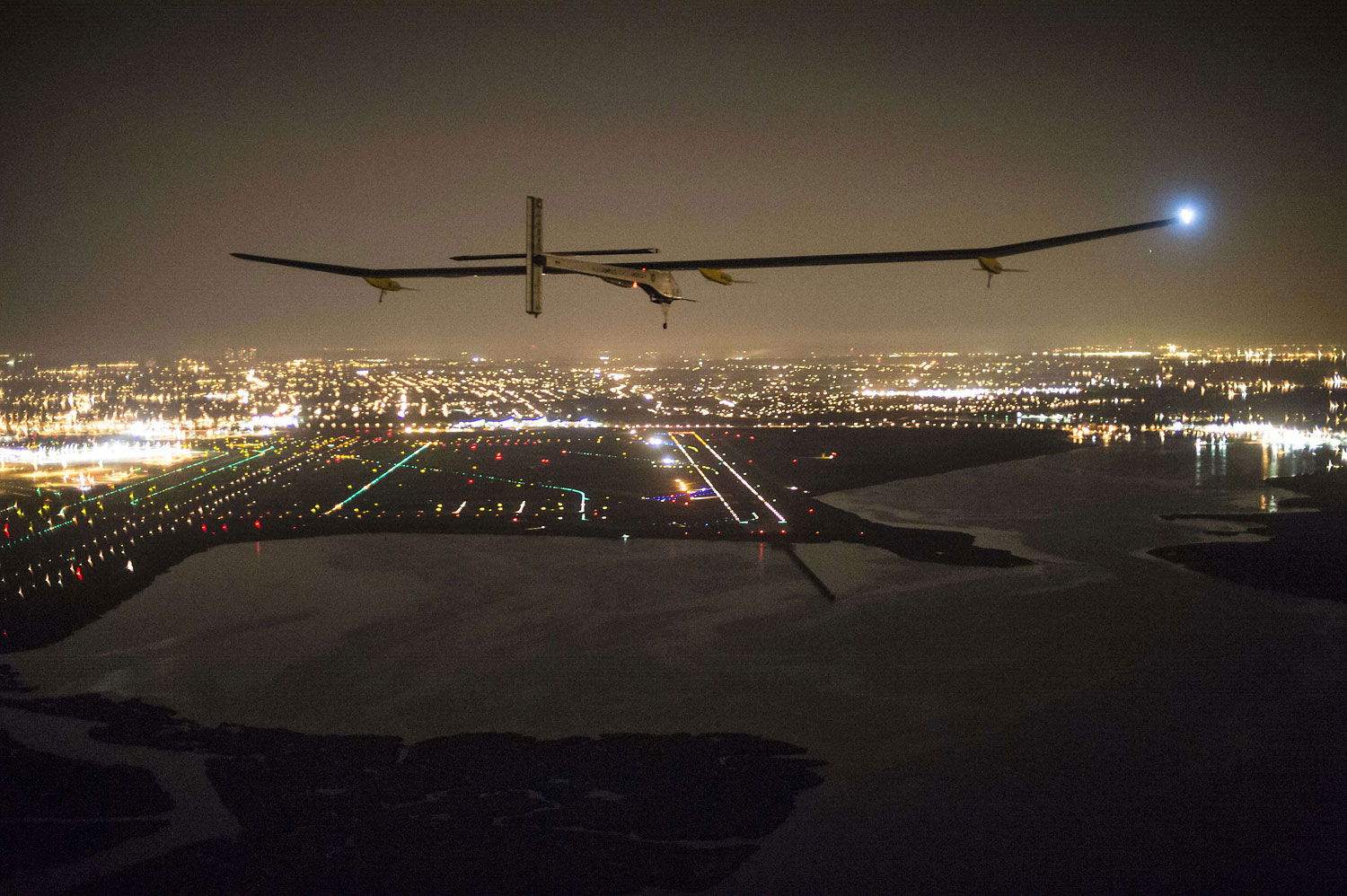 Solar Impulse, with Andre Borschberg onboard, approaches JFK airport on late July 6, 2013 in New York. The experimental Solar Impulse plane, powered by the sun, completed a transcontinental trip across the United States late Saturday, touching down in New York despite a rip in the fabric of one wing.