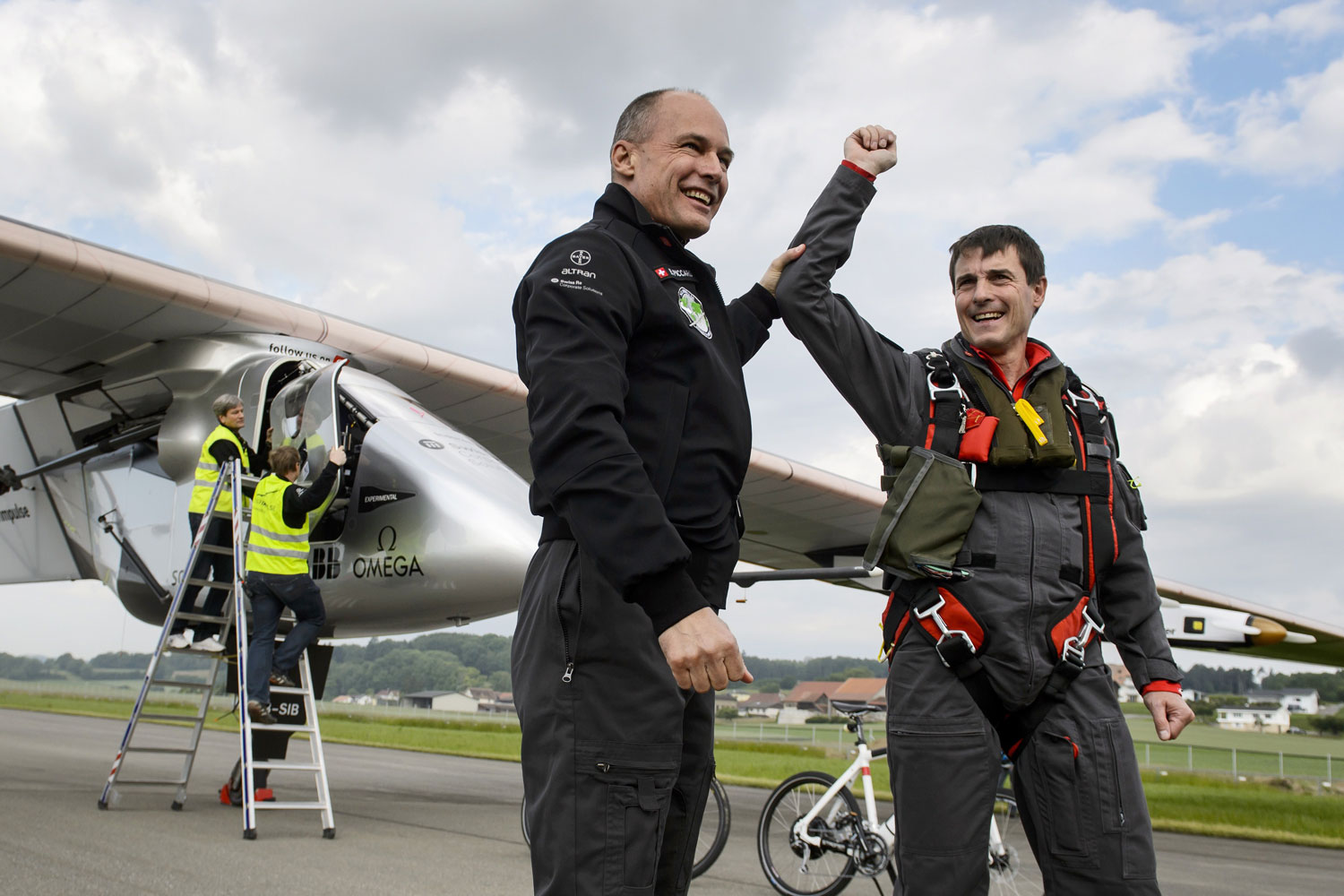 From left: Solar Impulse co-founder Bertrand Piccard congratulates German test pilot Markus Scherdel after Solar Impulse 2's maiden flight from Payerne on  June 2, 2014.