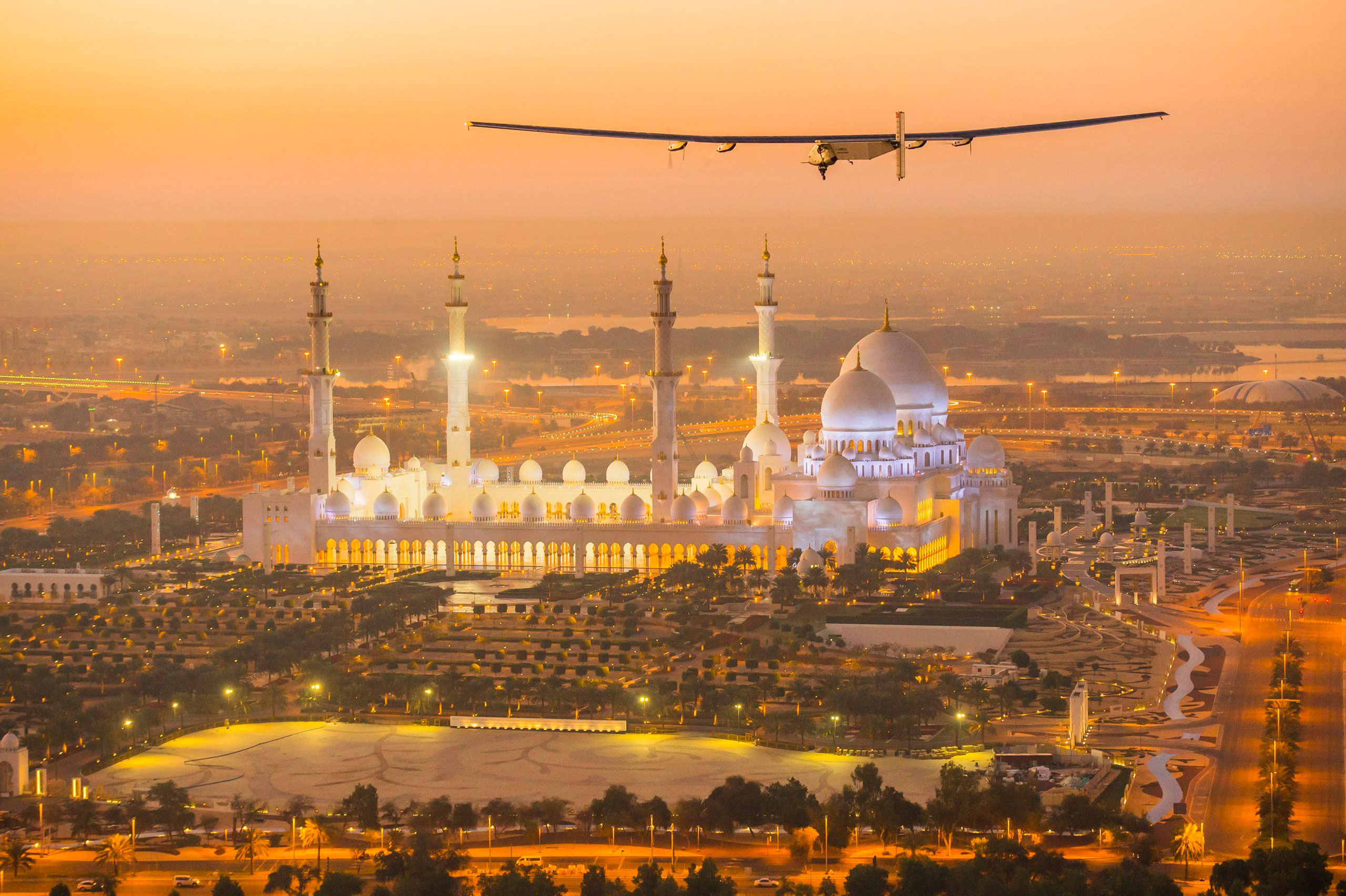 The Solar Impulse 2, a solar-powered plane, flies over the Sheikh Zayed Grand Mosque in Abu Dhabi during preparations for next month's round-the-world flight on Feb. 26, 2015.