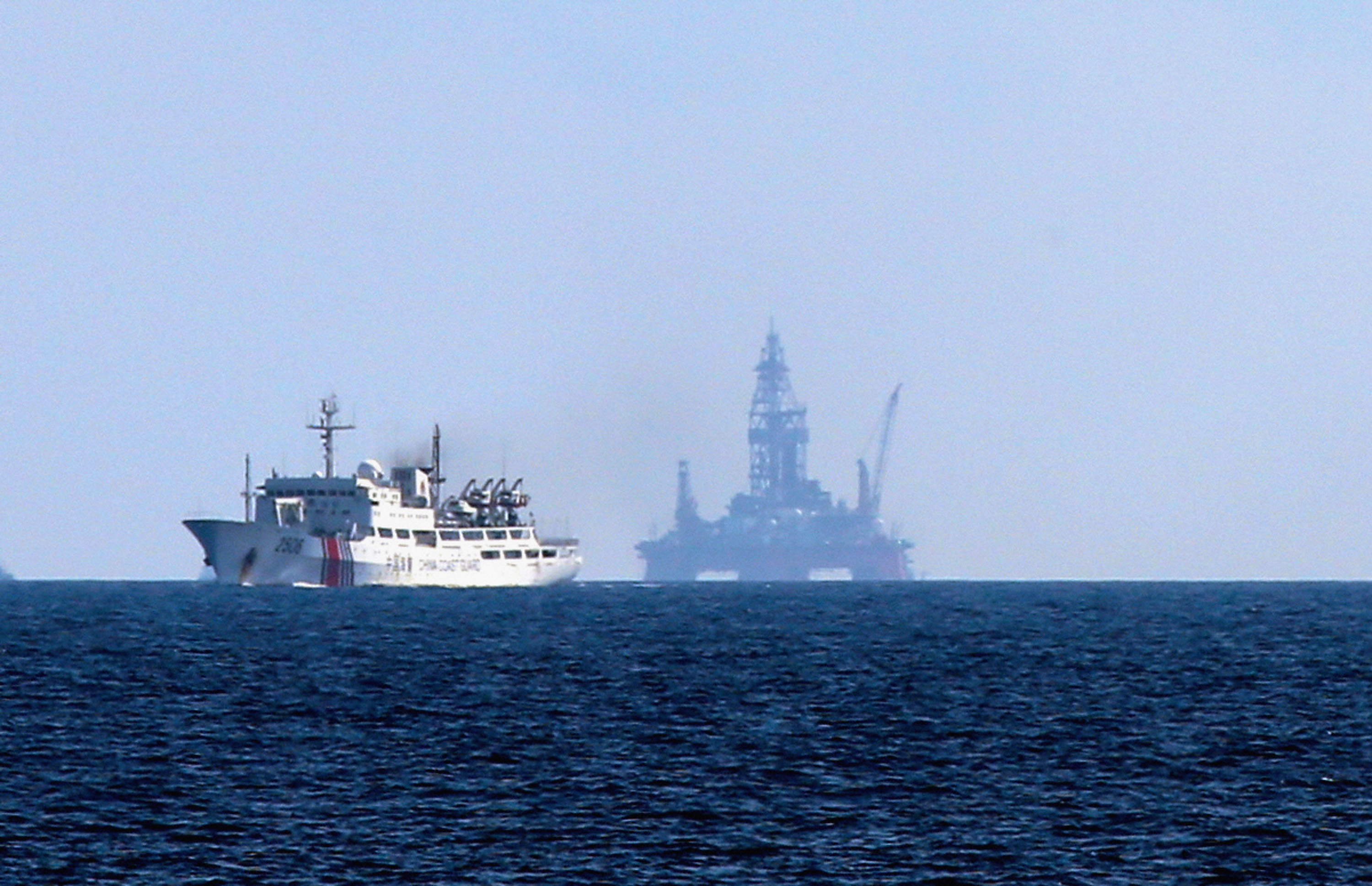 A Chinese coast guard ship navigates around Chinese drilling equipment located in waters off the disputed Paracel Islands on May 28, 2014.