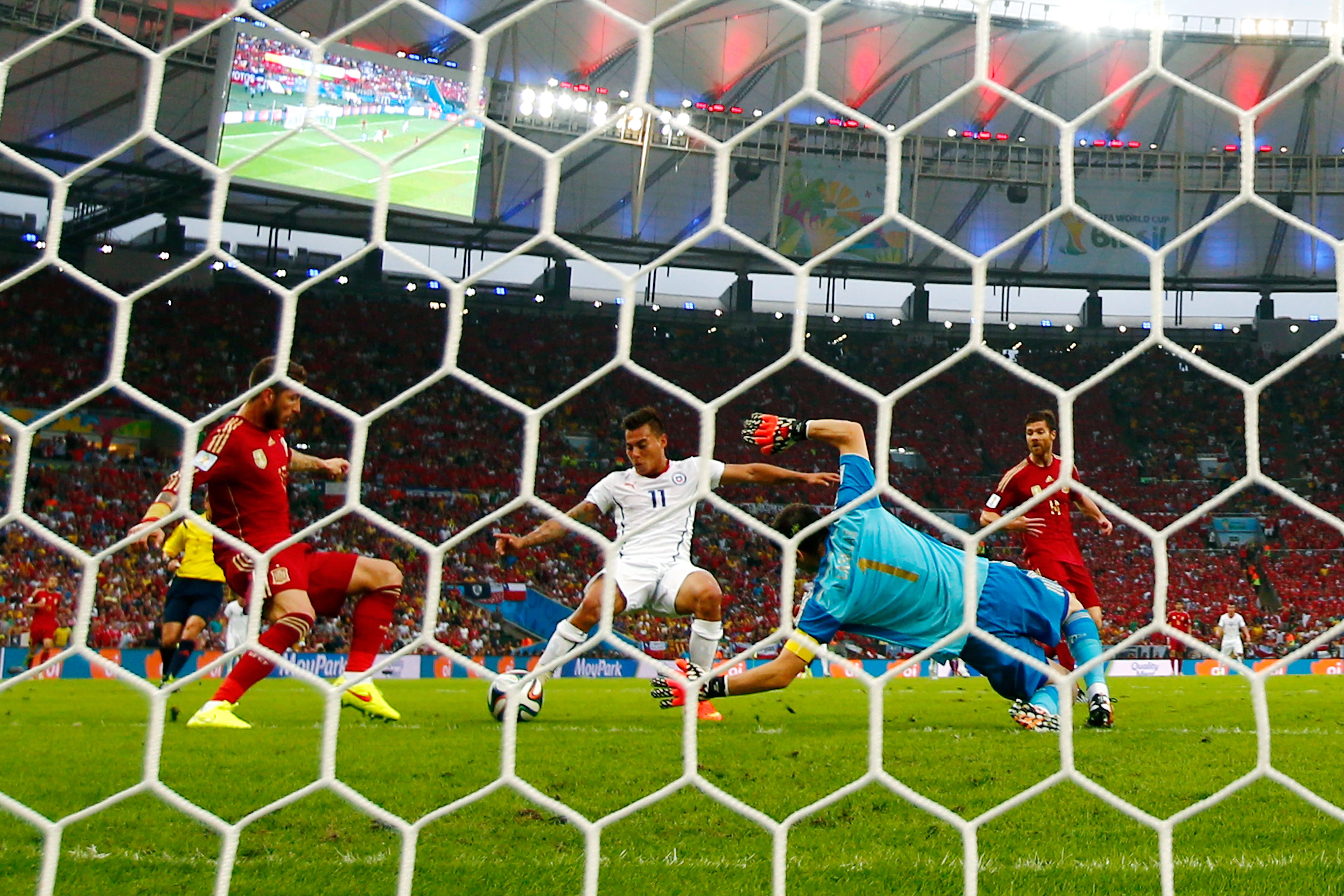 Eduardo Vargas of Chile shoots and scores his team's first goal past Sergio Ramos and goalkeeper Iker Casillas of Spain during the 2014 FIFA World Cup Brazil Group B match between Spain and Chile at Maracana on June 18, 2014 in Rio de Janeiro.